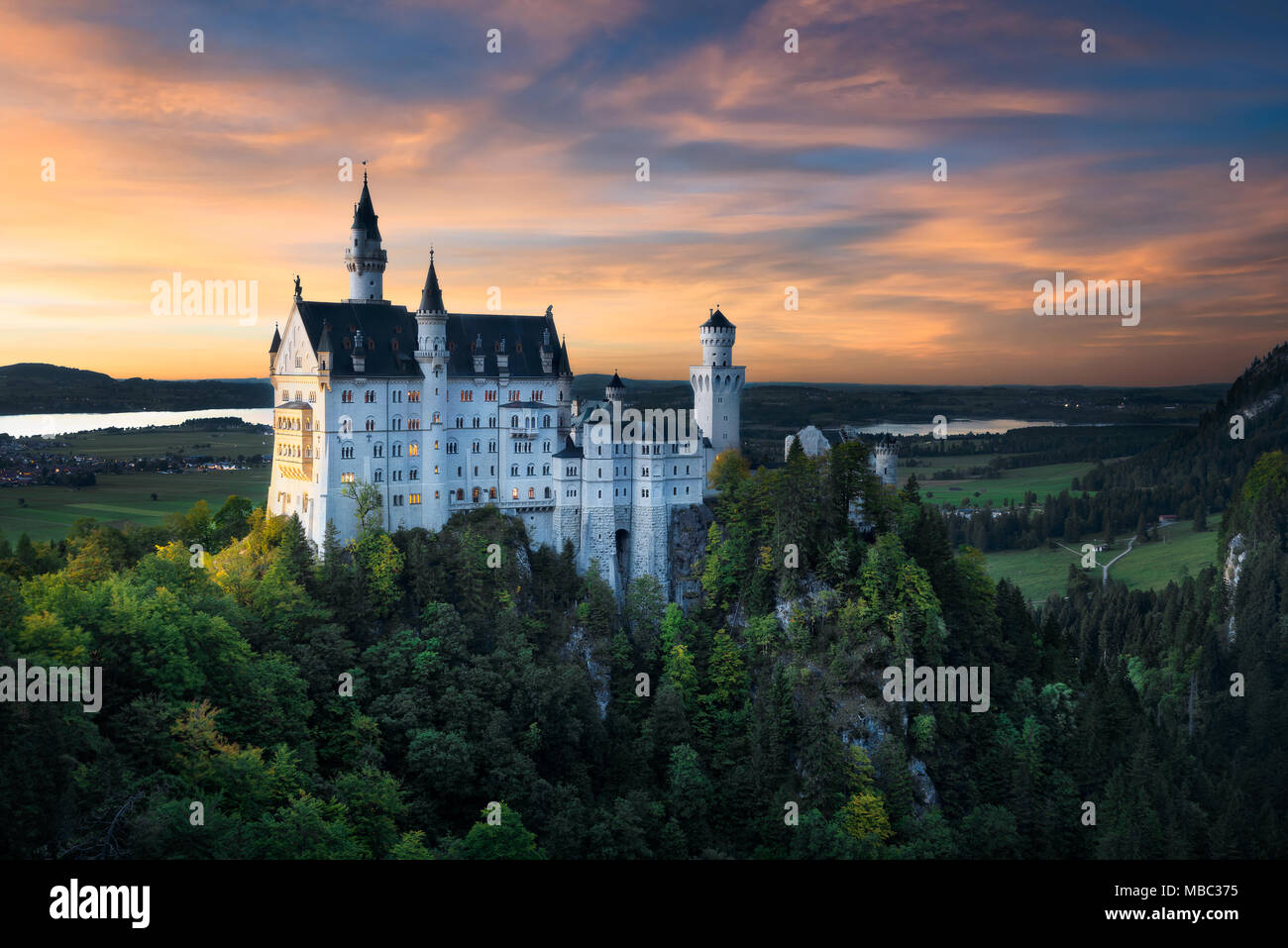 Beautiful view of world-famous Neuschwanstein Castle. Colorful sky during sunset. Autumn colors of forest. Scenic mountain landscape near Fussen, sout - Stock Image