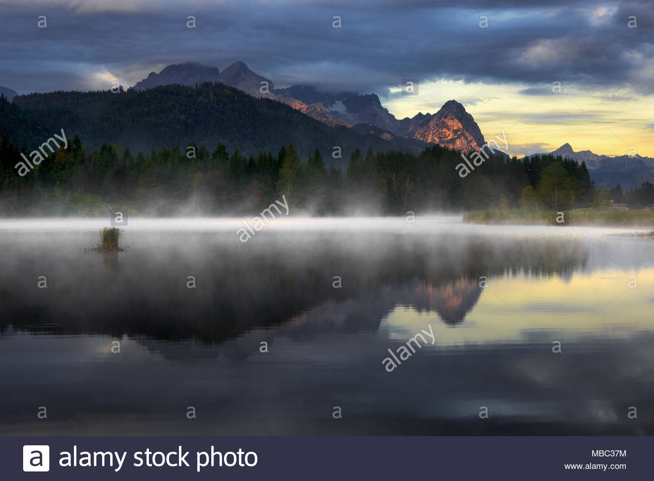 Wetterstein mountain reflection during autumn day with morning fog over Geroldsee lake, Bavarian Alps, Bavaria, Germany. - Stock Image
