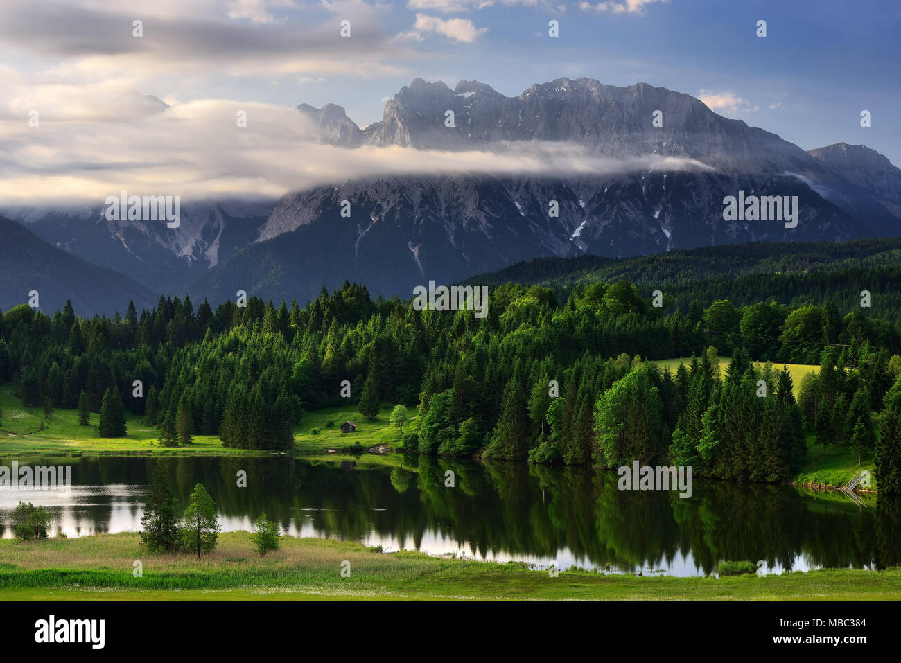 Geroldsee lake during morning sunrise with foggy clouds over mountain peaks, Bavarian Alps, Bavaria, Germany. - Stock Image