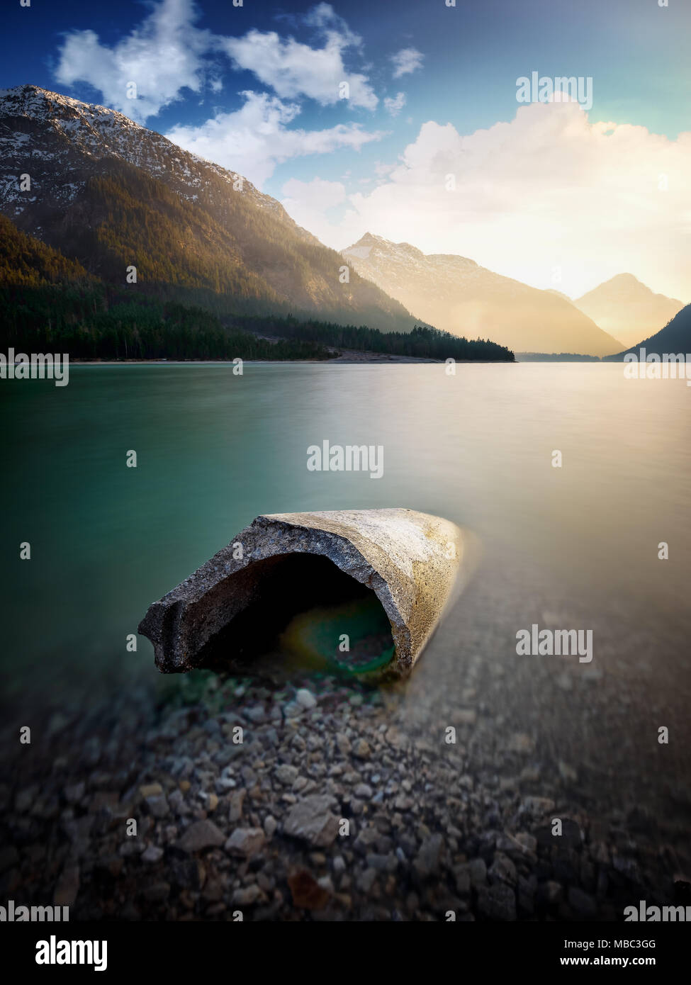 Landscape of Plansee lake and Alps mountains. Concrete block lying in lake, Tyrol, Austria - Stock Image
