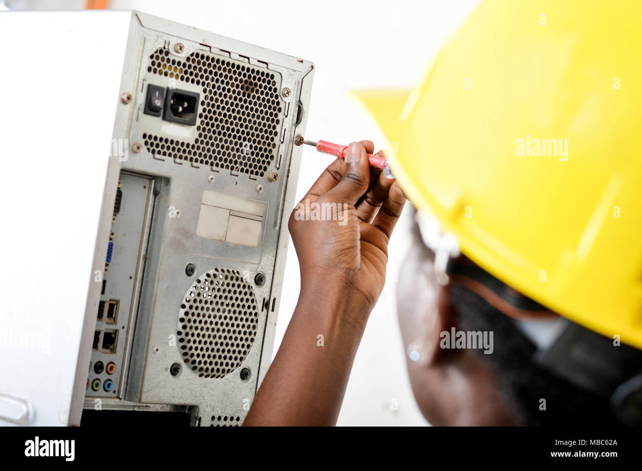 Close-up of a worker's head opening a computer with a vice turn. - Stock Image