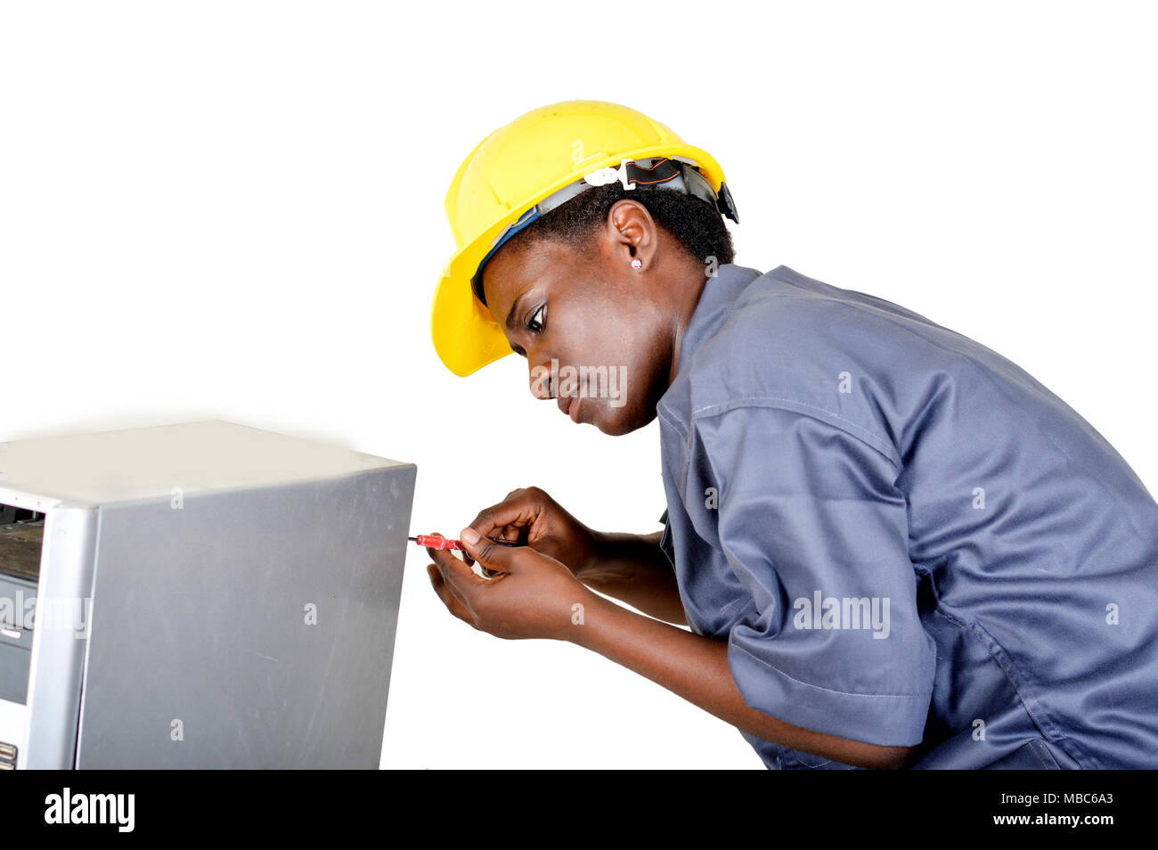 Young woman does the maintenance of a computer by disassembling it with a turn vice - Stock Image