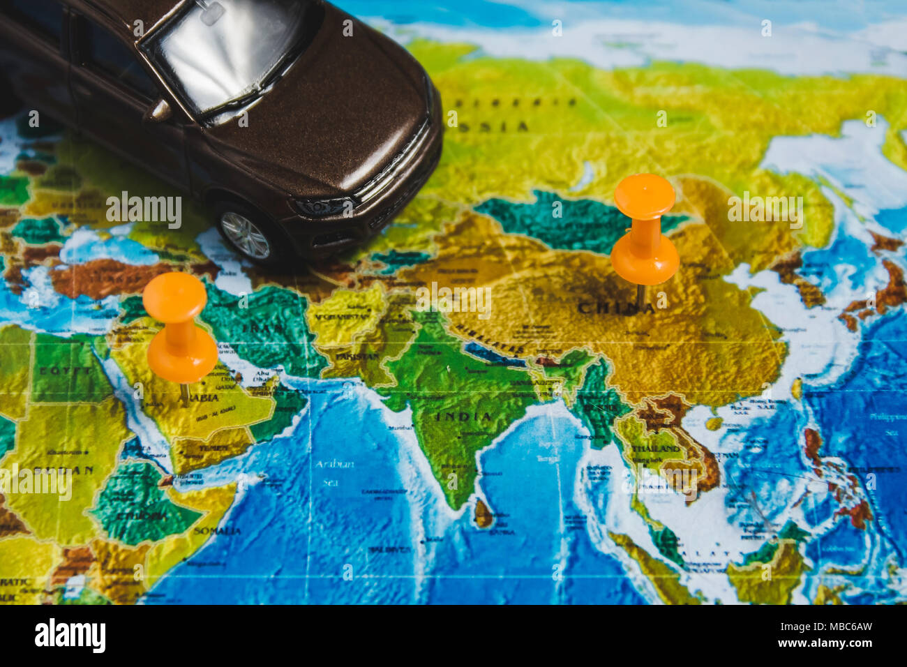 automotive travel destination points on world map indicated with colorful thumbtacks and shallow depth of field
