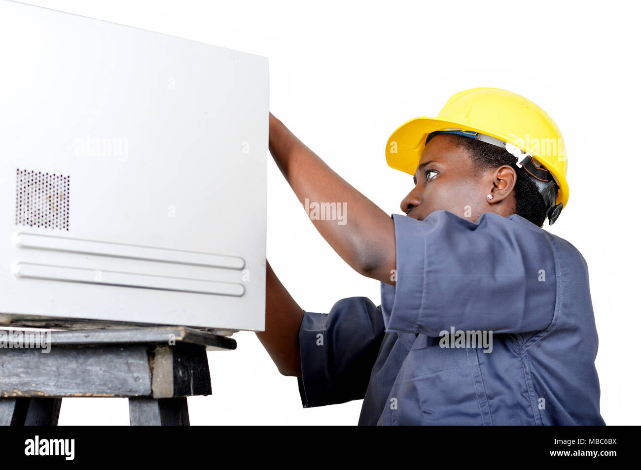 Close-up of a young woman doing the maintenance of a desktop computer. - Stock Image