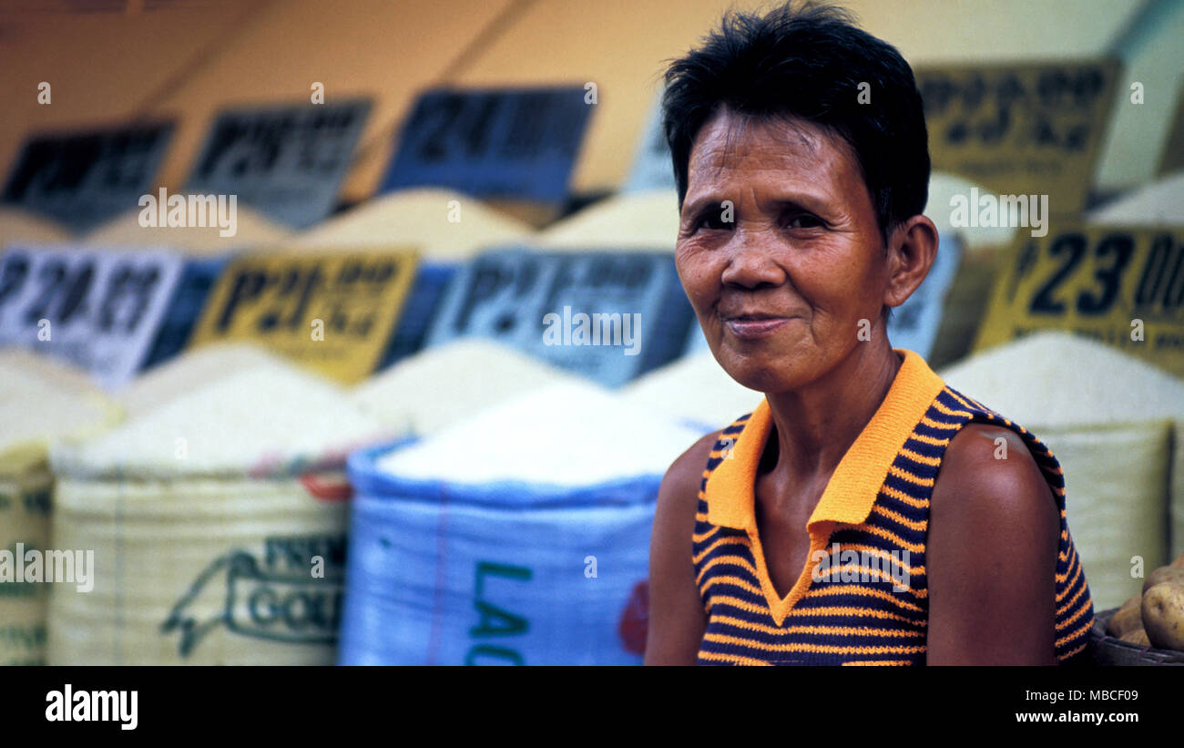 A Filipina woman selling rice and other grains at a local market in Manila, the Philippines. - Stock Image