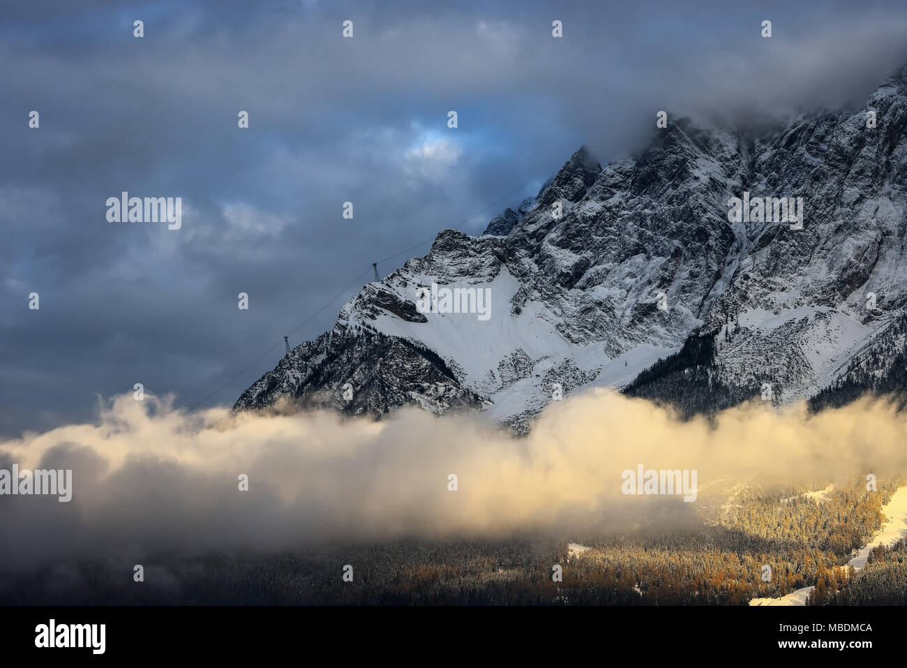 Amazing scene of Zugspitze mountain. Trees covered by snow. Heavy clouds over mountains. Ammergau Alps. Typical winter scene at mountain. Bavarian pea - Stock Image