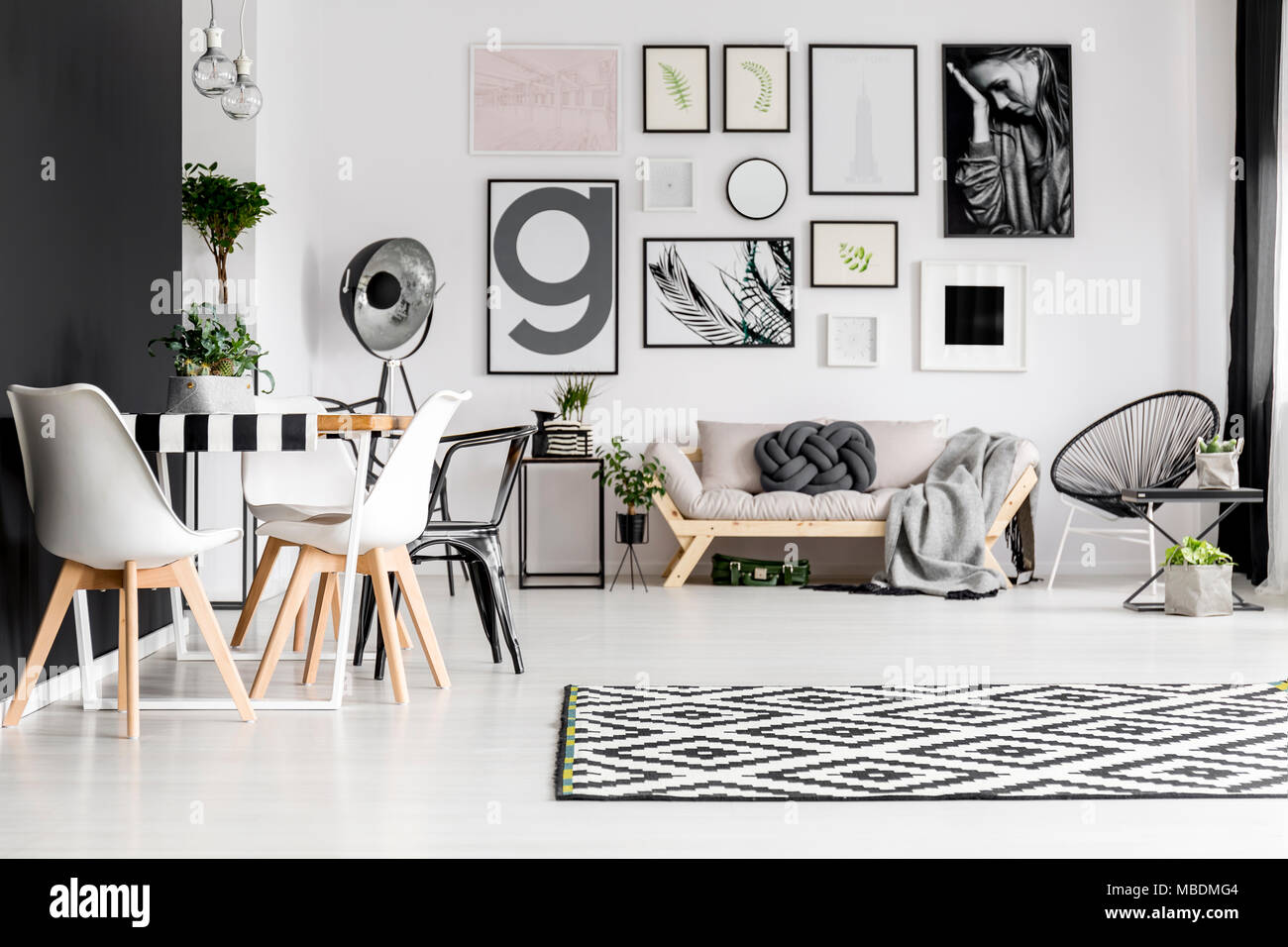 Art Gallery Dining Table With Chairs And Sofa Blanket Knot Pillow In A White Living Room Interior