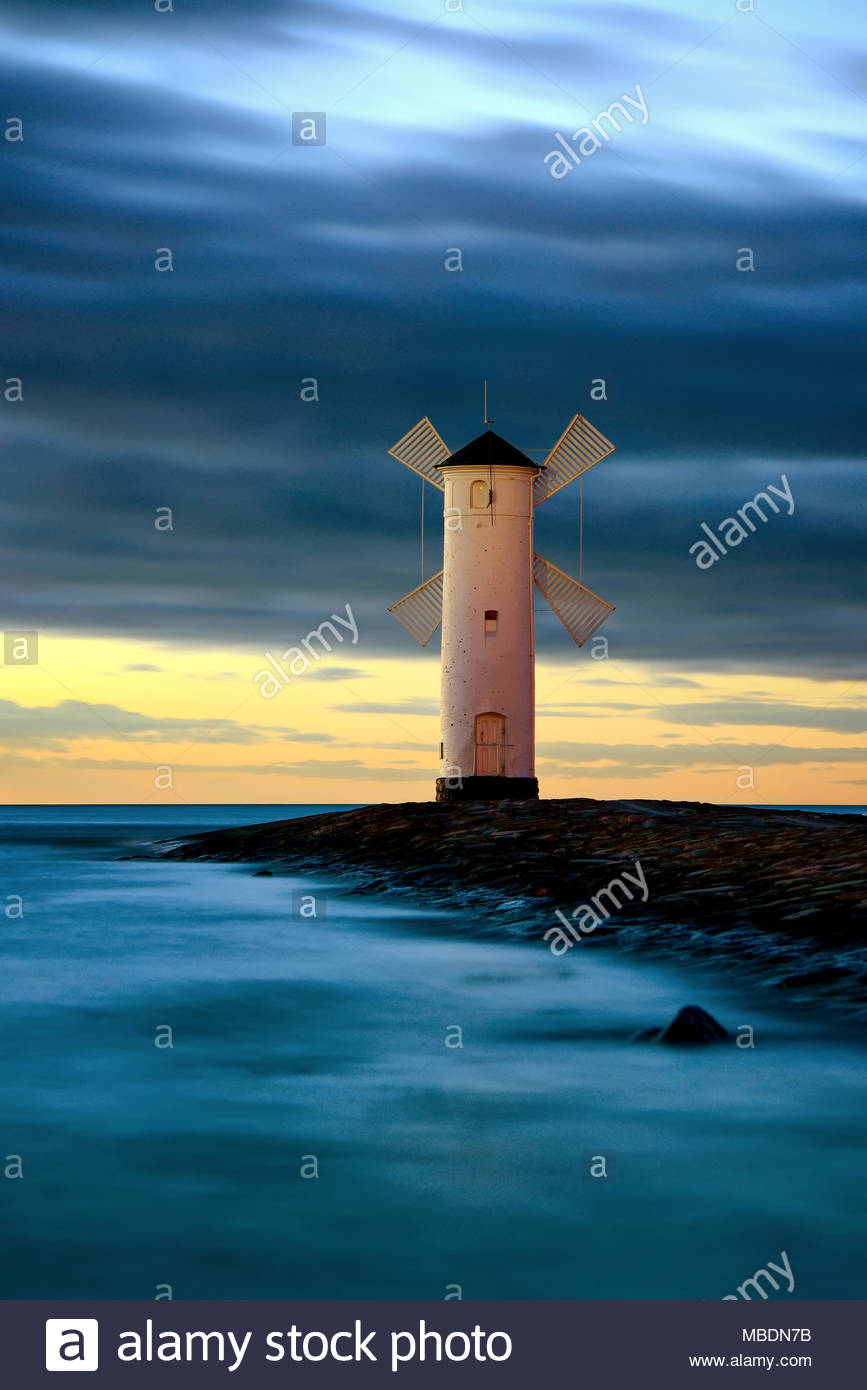 Dramatic Baltic sea scene. Cold winter evening. Heavy cloudy sky. Beautiful sunset over a windmill-shaped lighthouse. Swinoujscie, Poland. - Stock Image