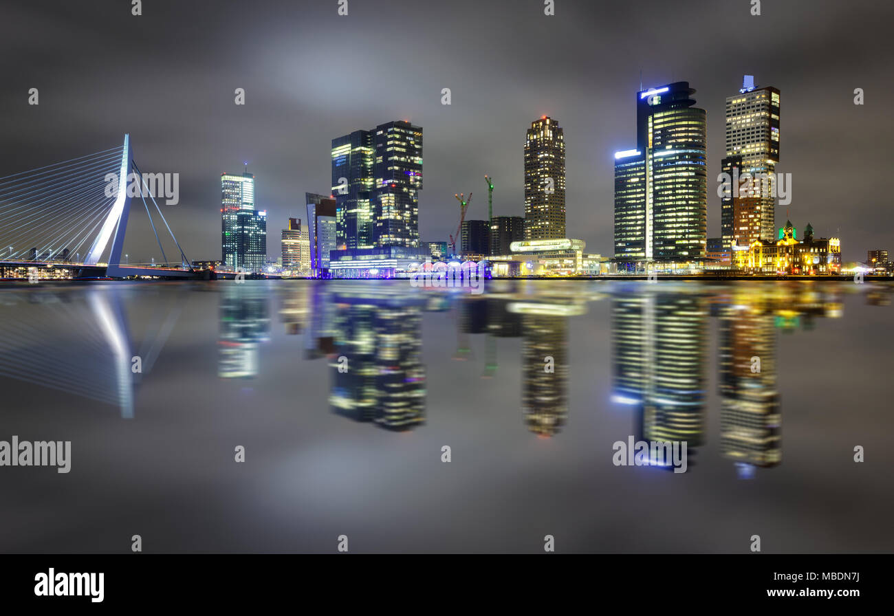 Amazing night reflection of Erasmus bridge and several skyscrapers in Rotterdam, Holland. Fascinating modern architecture. - Stock Image