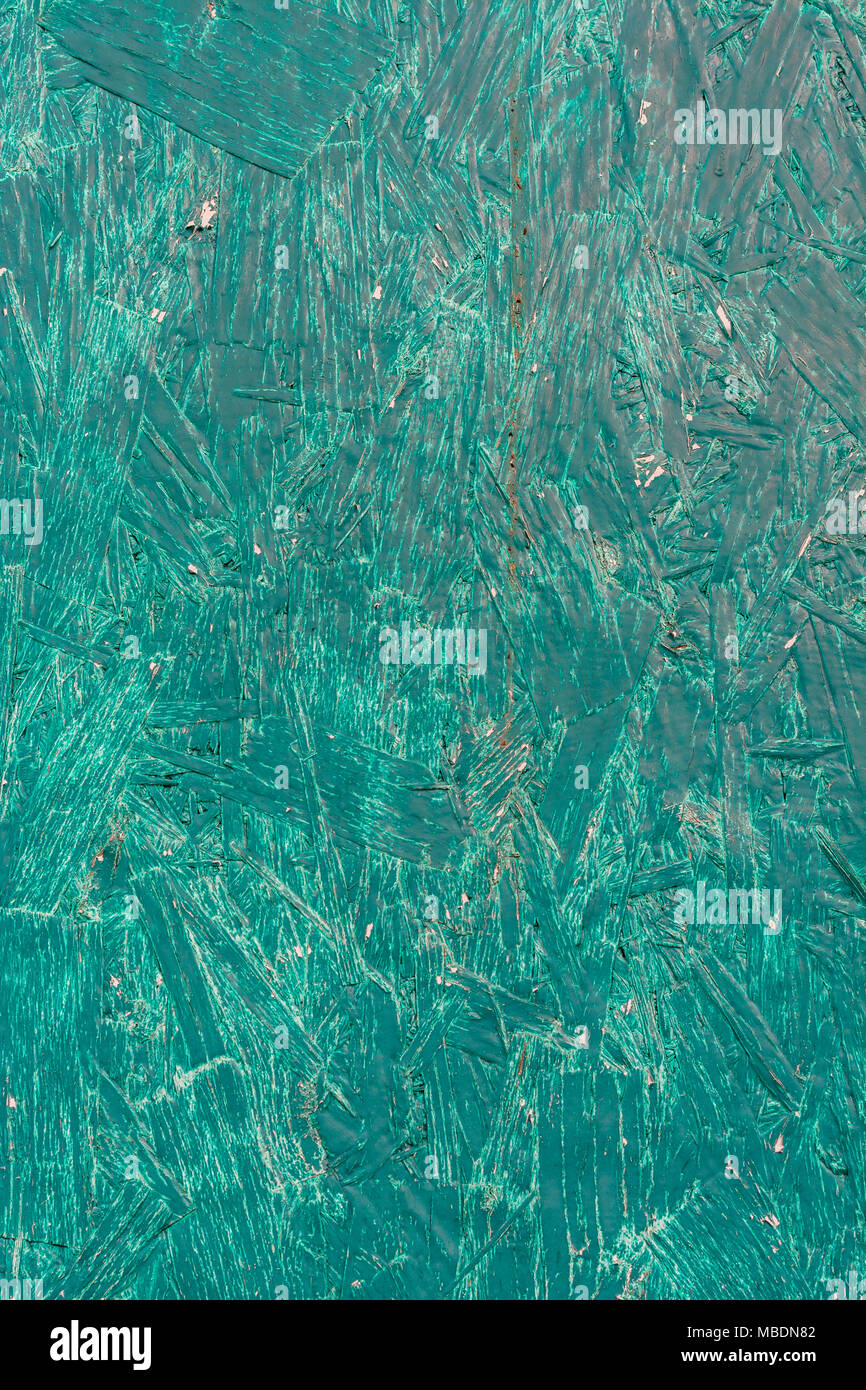 Close-up of the brushstrokes of a piece of green painted plywood. - Stock Image