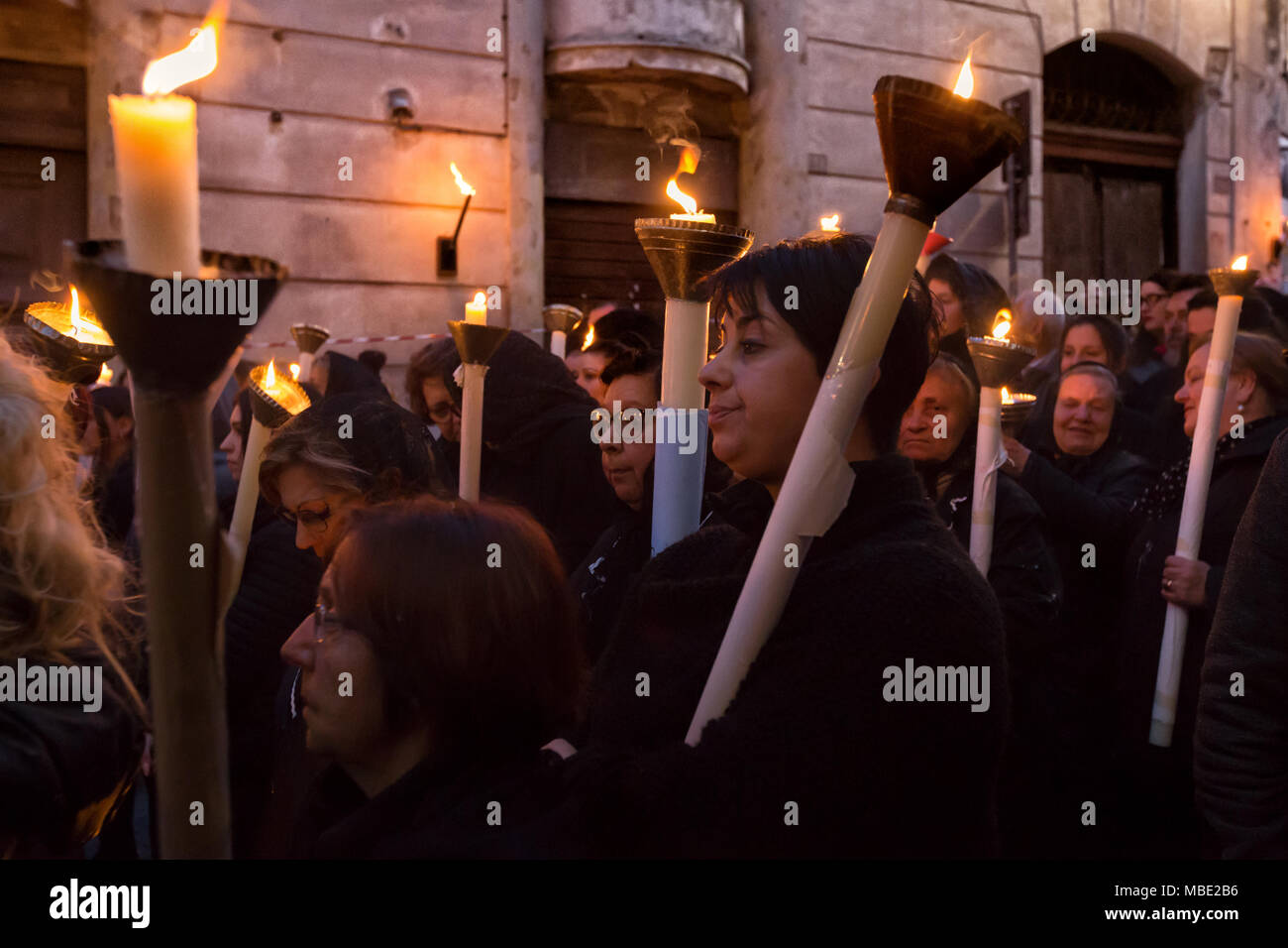 SESSA AURUNCA, ITALY - MARCH 30-31, 2018 - Holy week in Sessa Aurunca, southern Italy, is celebrated with some religious rites. On Good Friday, at sunset, the parade of black hoods slowly walks through the streets of the town. At the bottom of the procession, a lot of women carry heavy candles and pray to Christ to receive the grace. - Stock Image