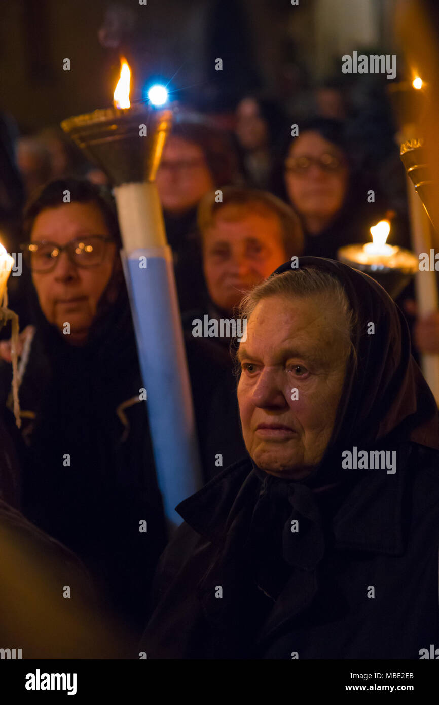 SESSA AURUNCA, ITALY - MARCH 30, 2018 - Women carry heavy candles and pray to Christ during the parade of black hoods in Sessa Aurunca, Italy, on Easter Good Friday - Stock Image