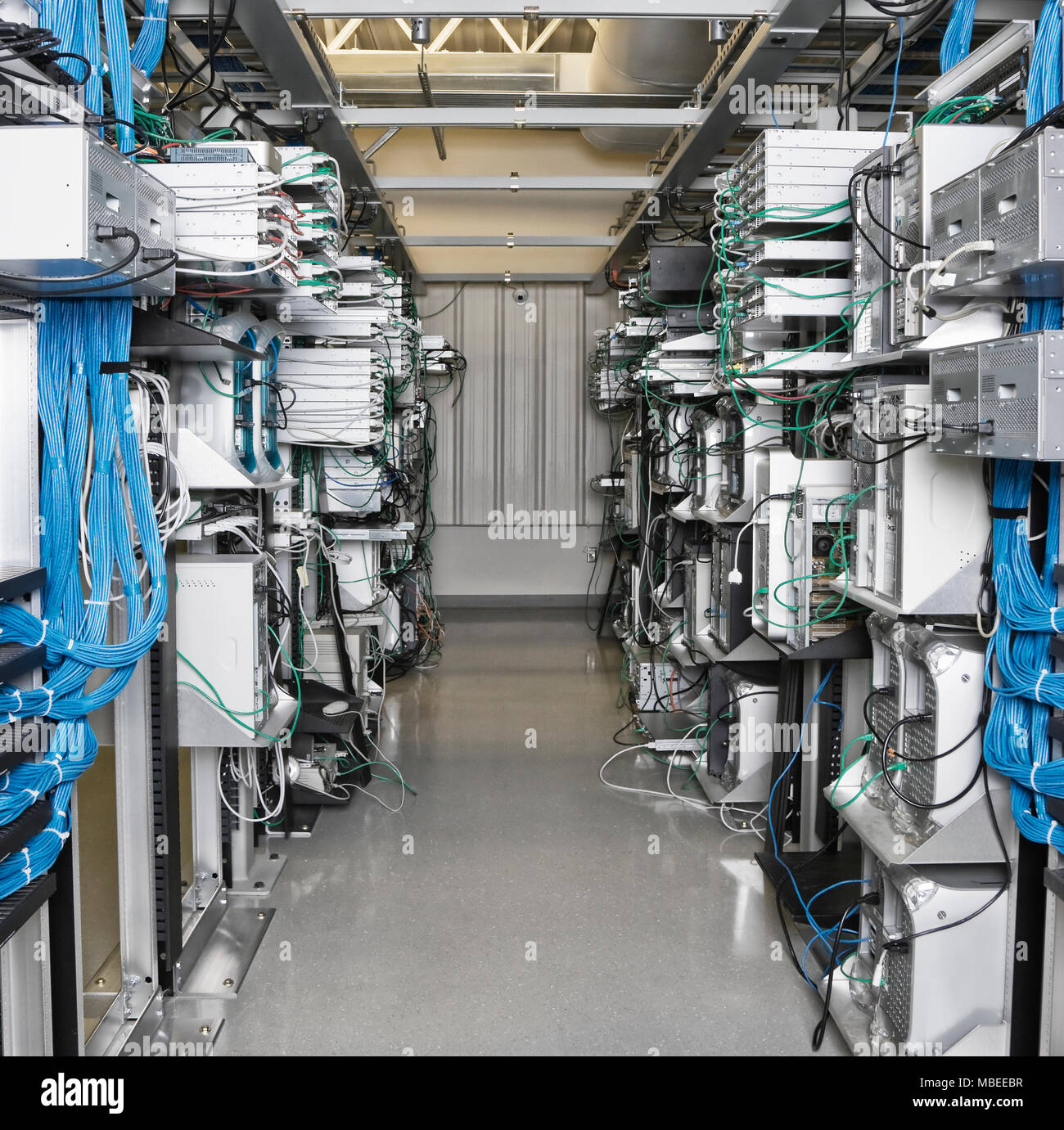 server room aisle showing computer servers and cat 5 cables stock