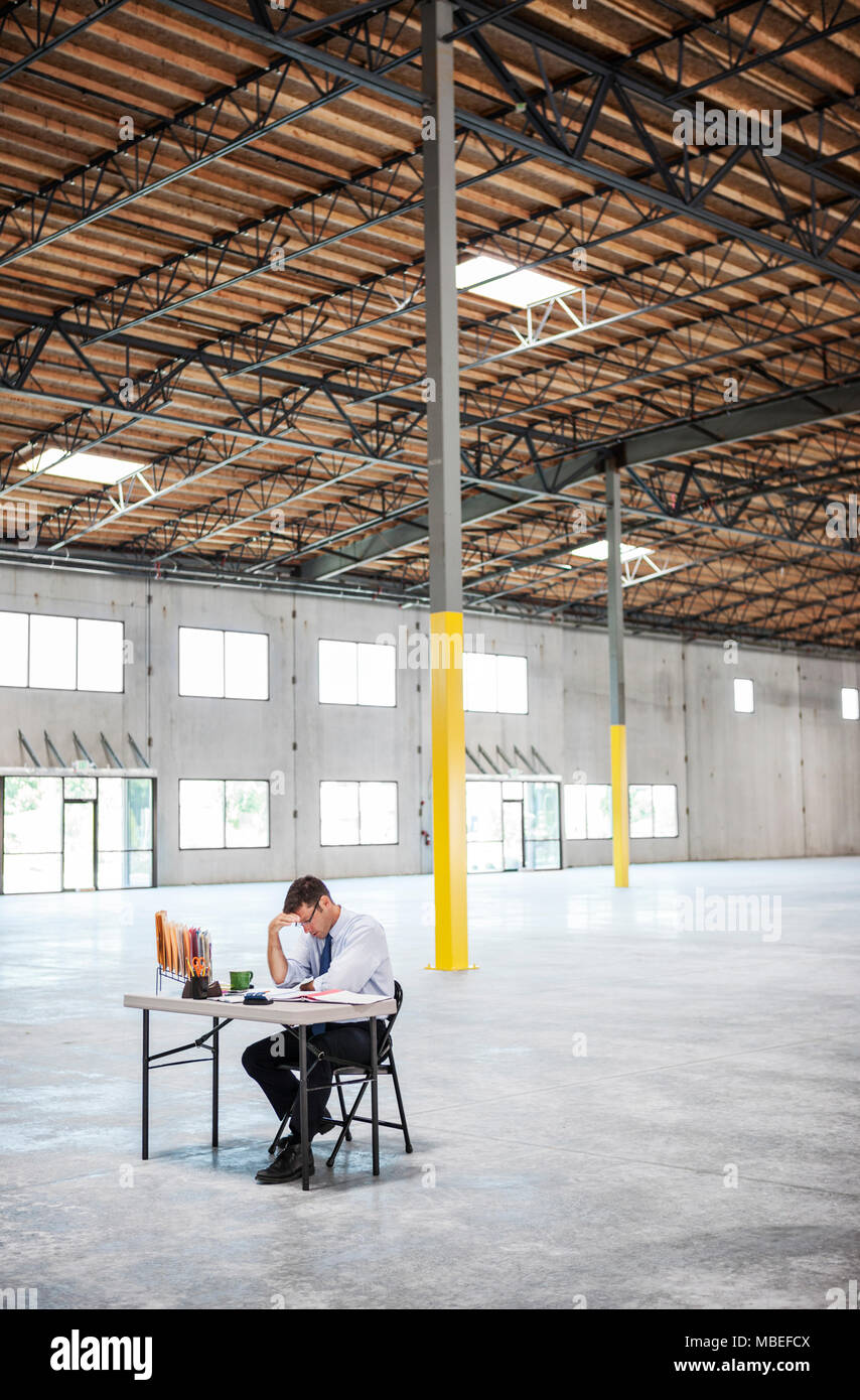 Caucasian Man Going Over Plans For New Warehouse Interior In Front