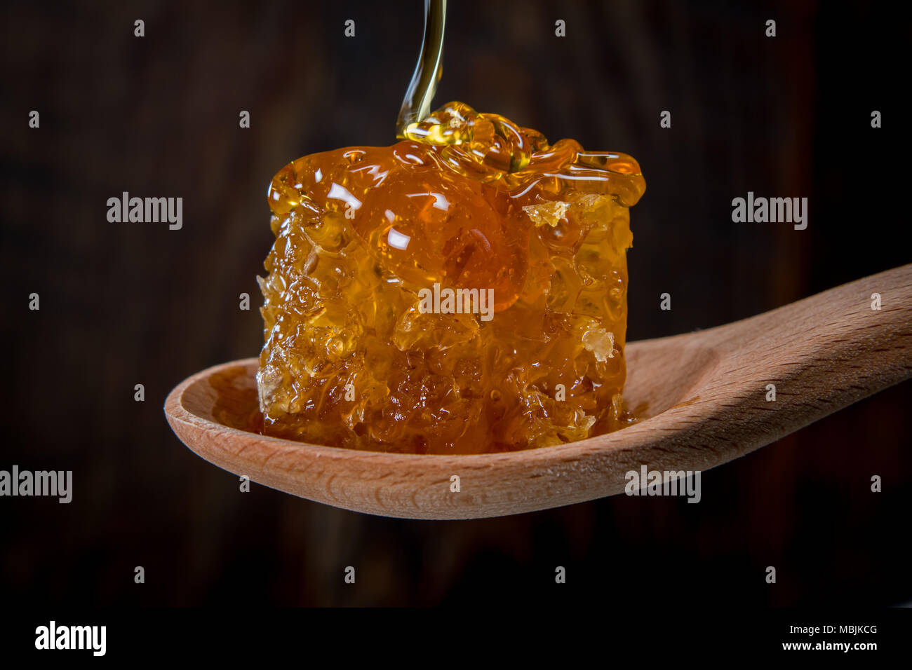 Drizzling Honey Over Comb sitting in wooden spoon - Stock Image