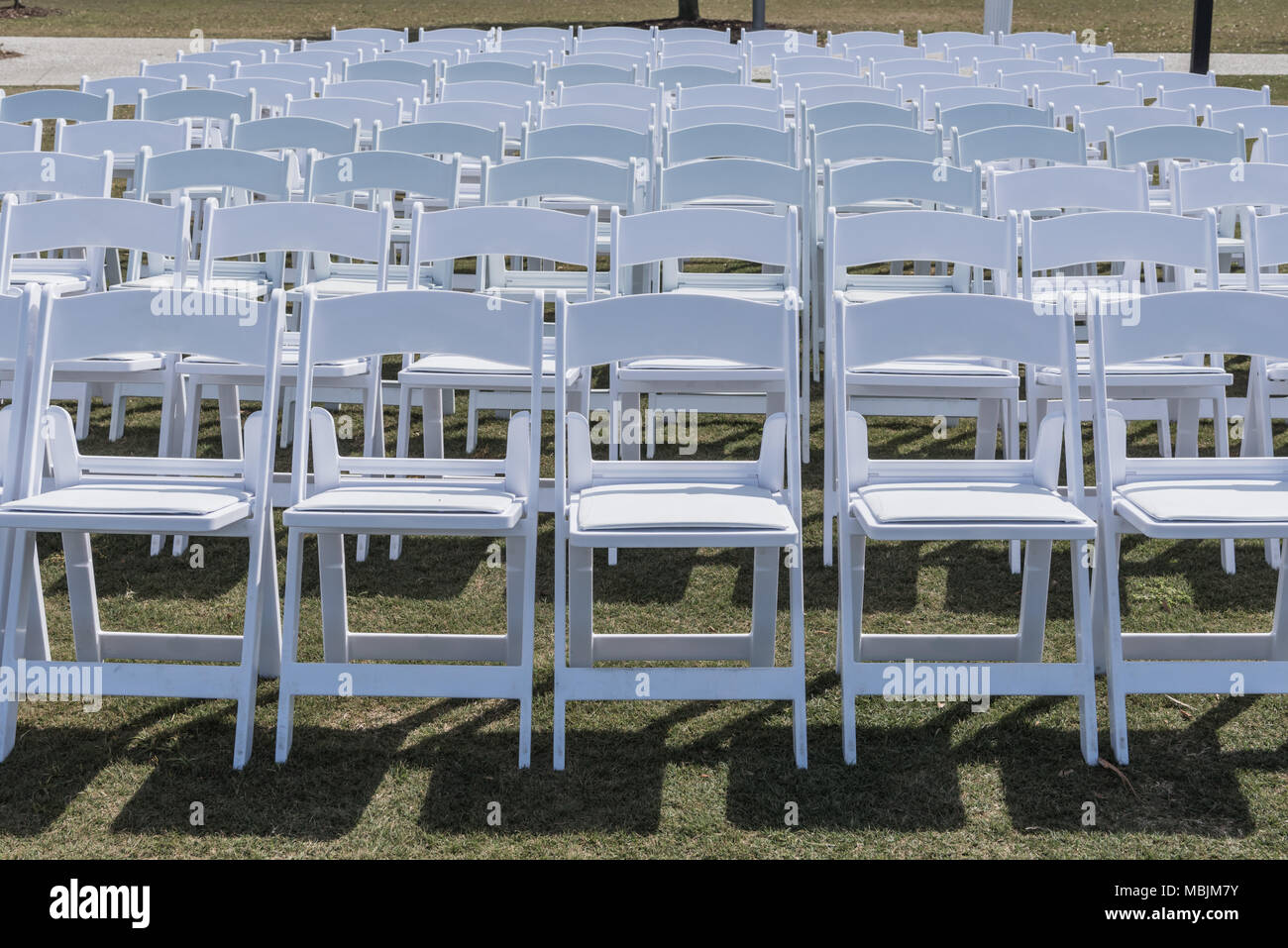 Empty Rows of White Chairs on grassy lawn - Stock Image