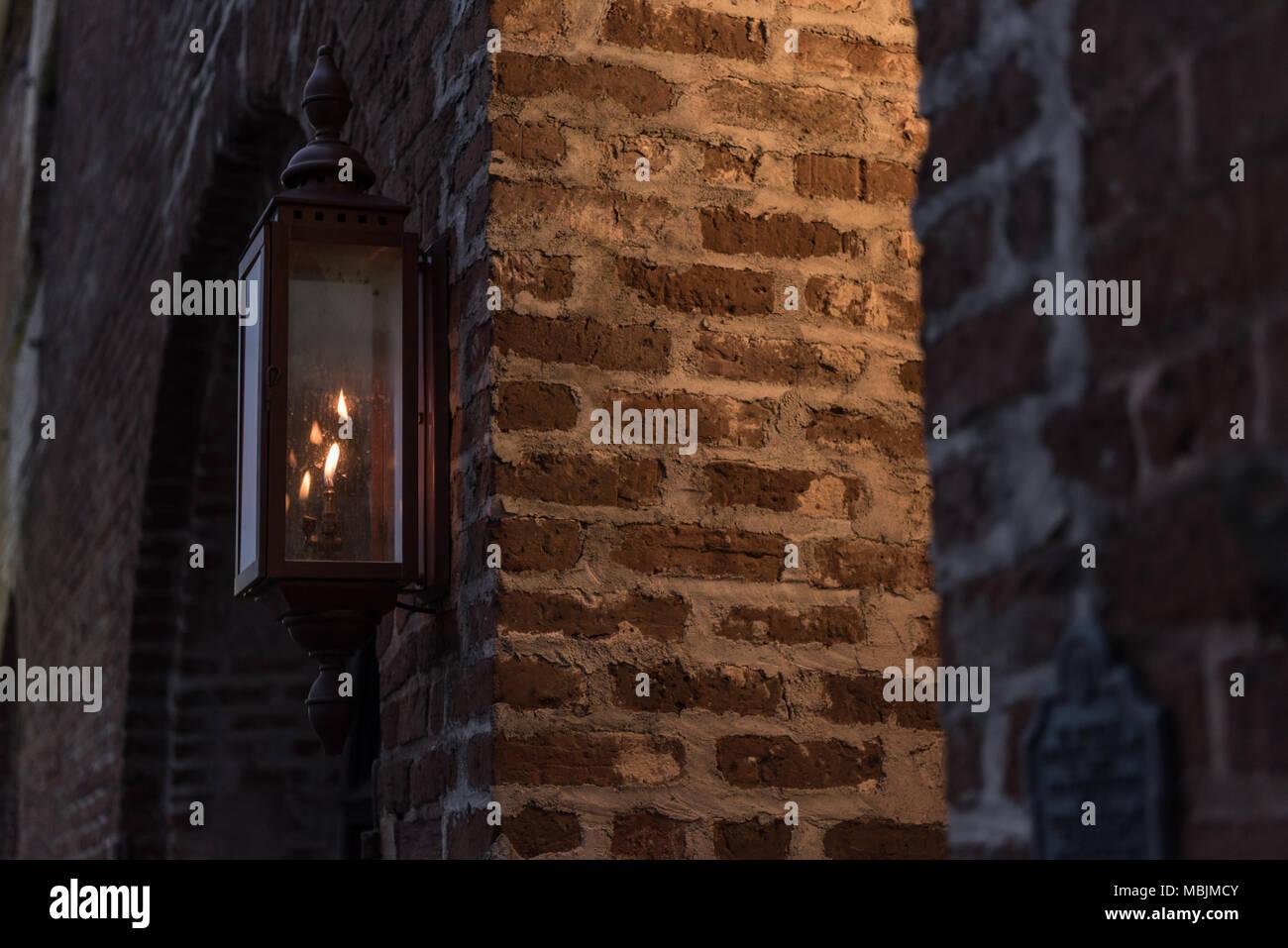 Gas Lamp Around the Corner of Lit Brick Wall - Stock Image