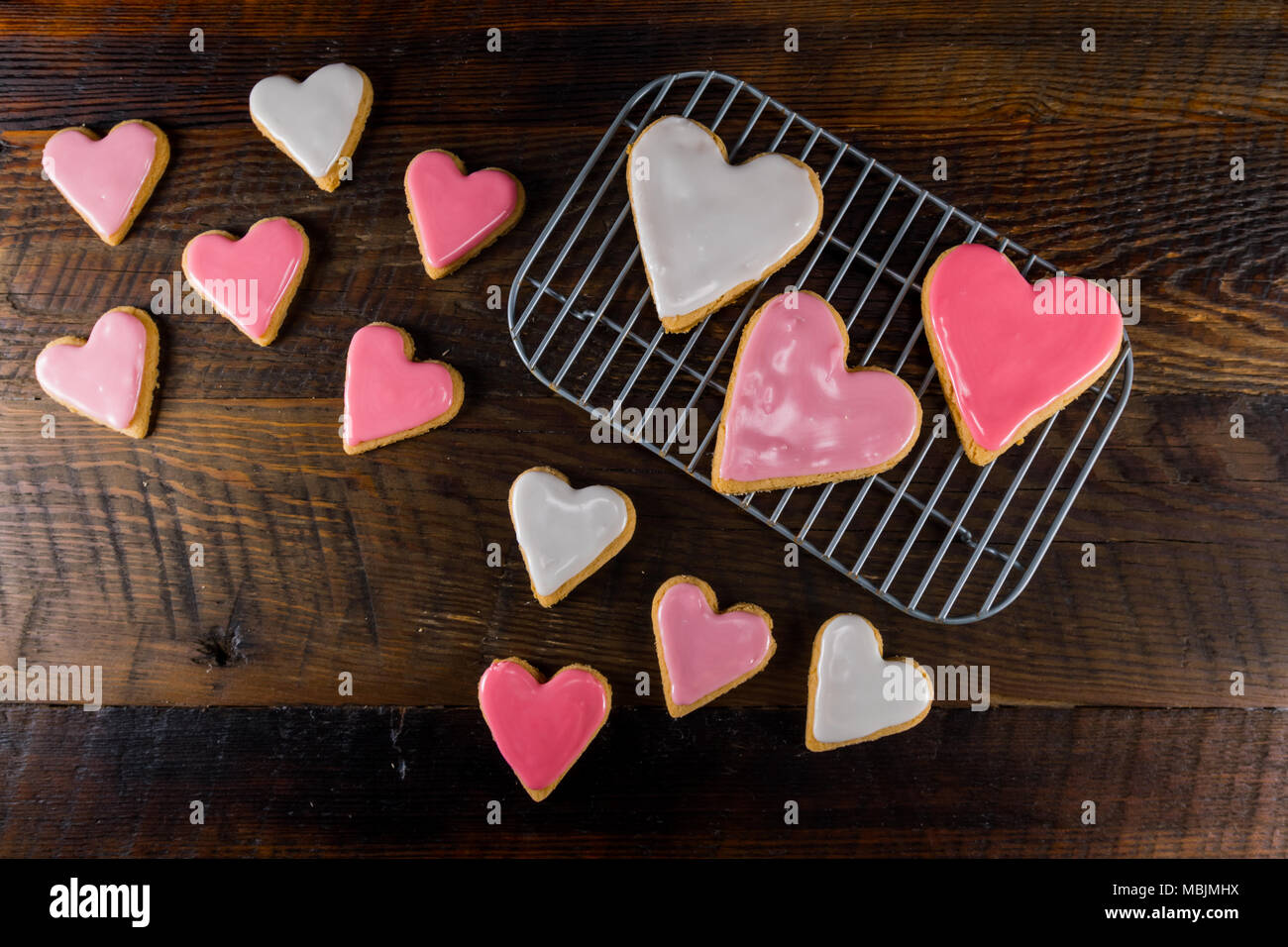 Heart Shaped Cookies On Cooling Rack and Table Top - Stock Image