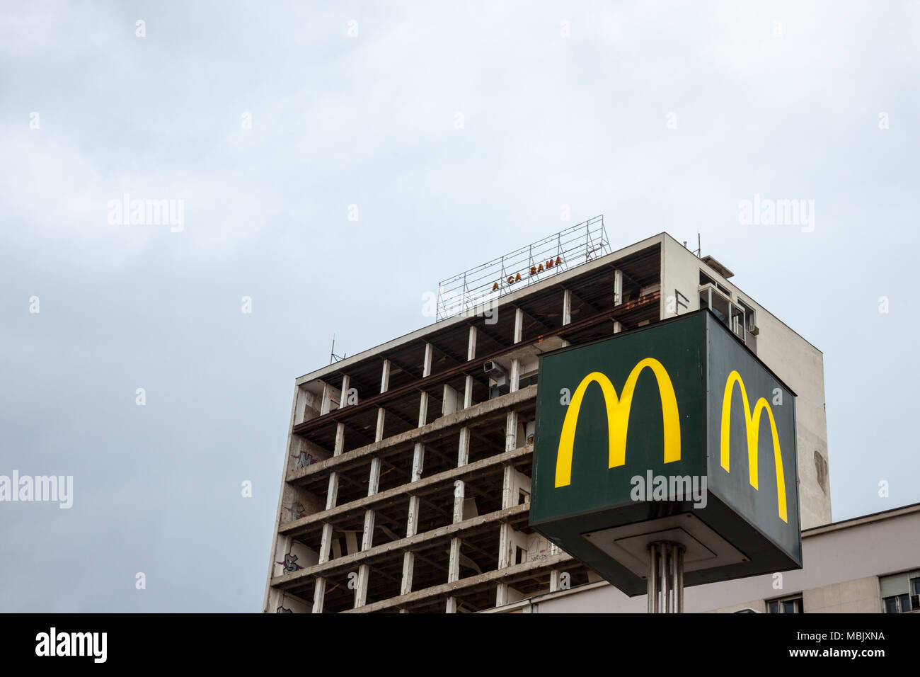 BELGRADE, SERBIA - MARCH 31, 2018: Mc Donald's logo with its iconic M in front of a half destroyed building in downtown Belgrade  Picture of a Mc Dona - Stock Image