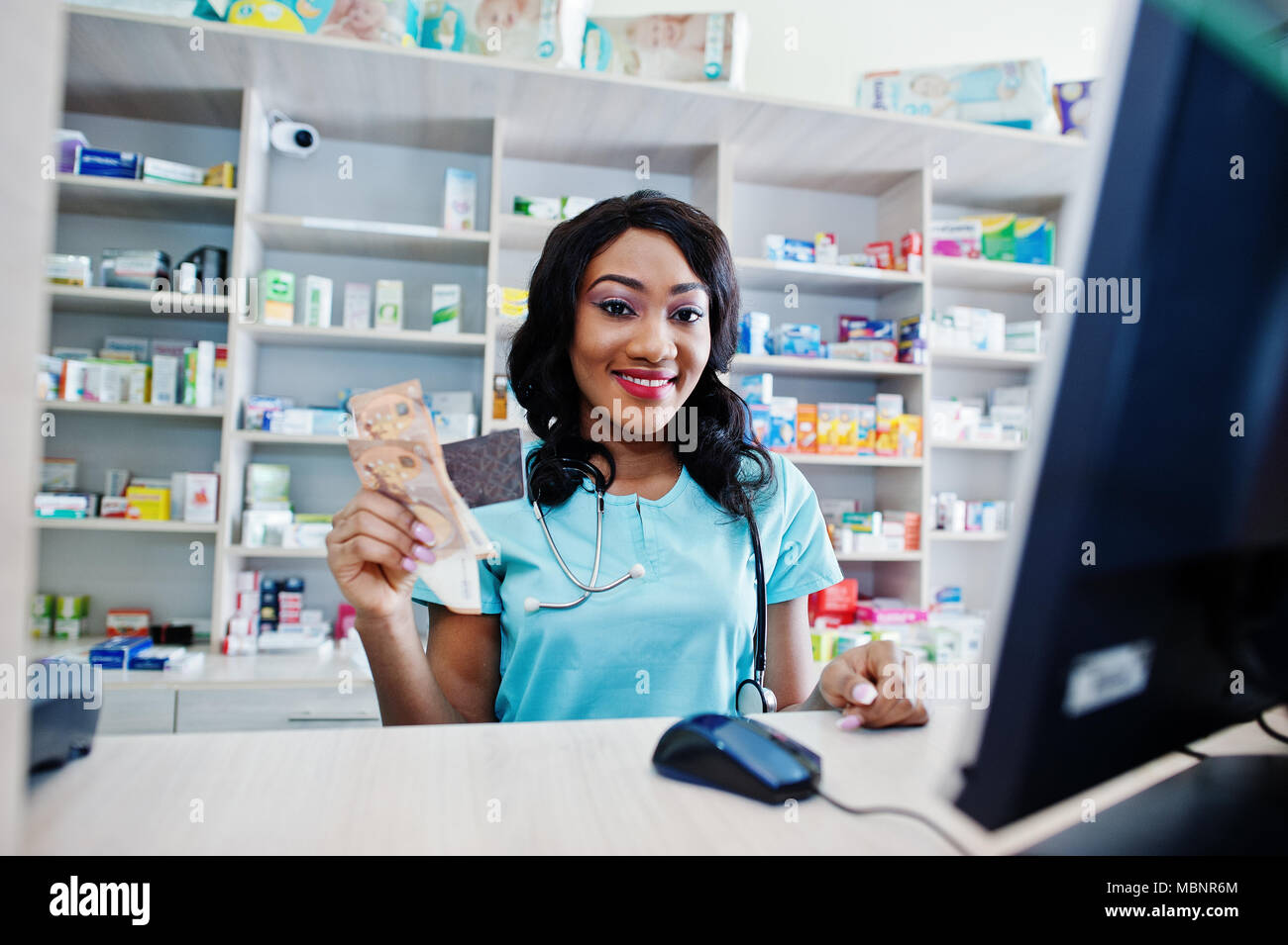 African American Pharmacist Working In Drugstore At Hospital