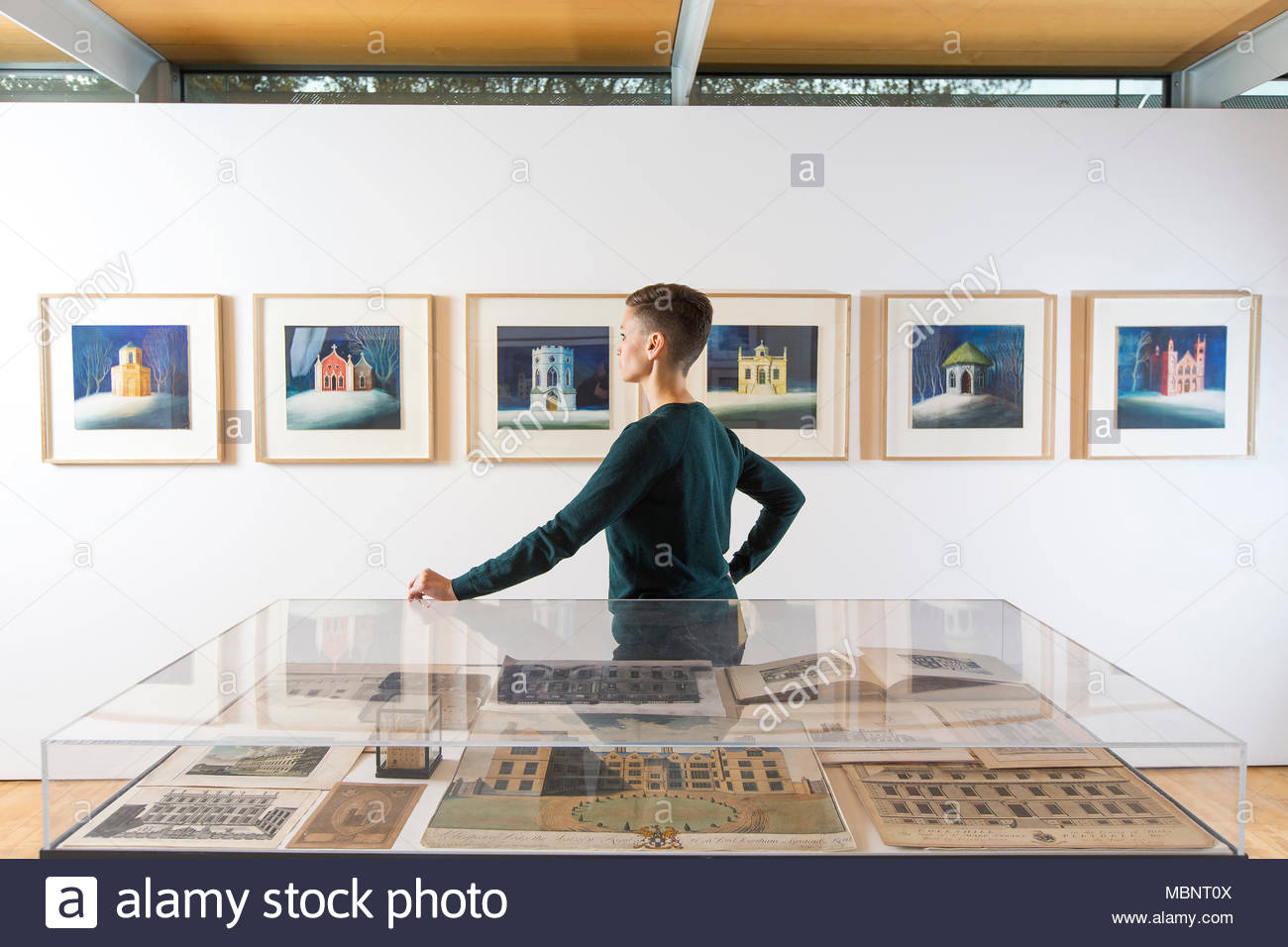A visitor looks at the Ed Kluz exhibition ' Sheer Folly-Fancifull Buildings of Britain' at Yorkshire Sculpture park. - Stock Image
