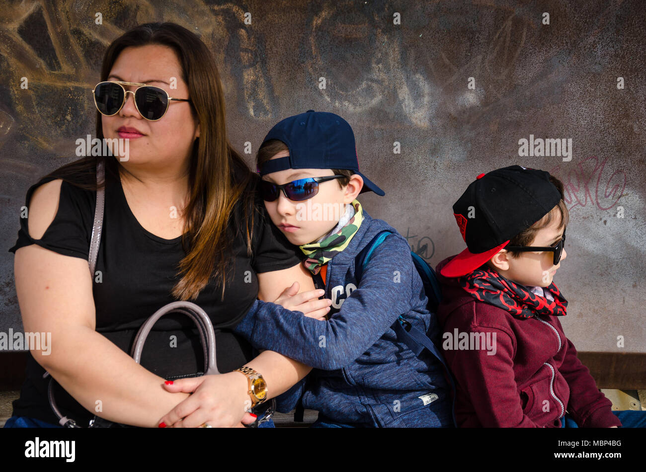 a-mother-sits-and-waits-with-her-two-young-children-for-a-train-while-on-holiday-in-spain-MBP4BG.jpg