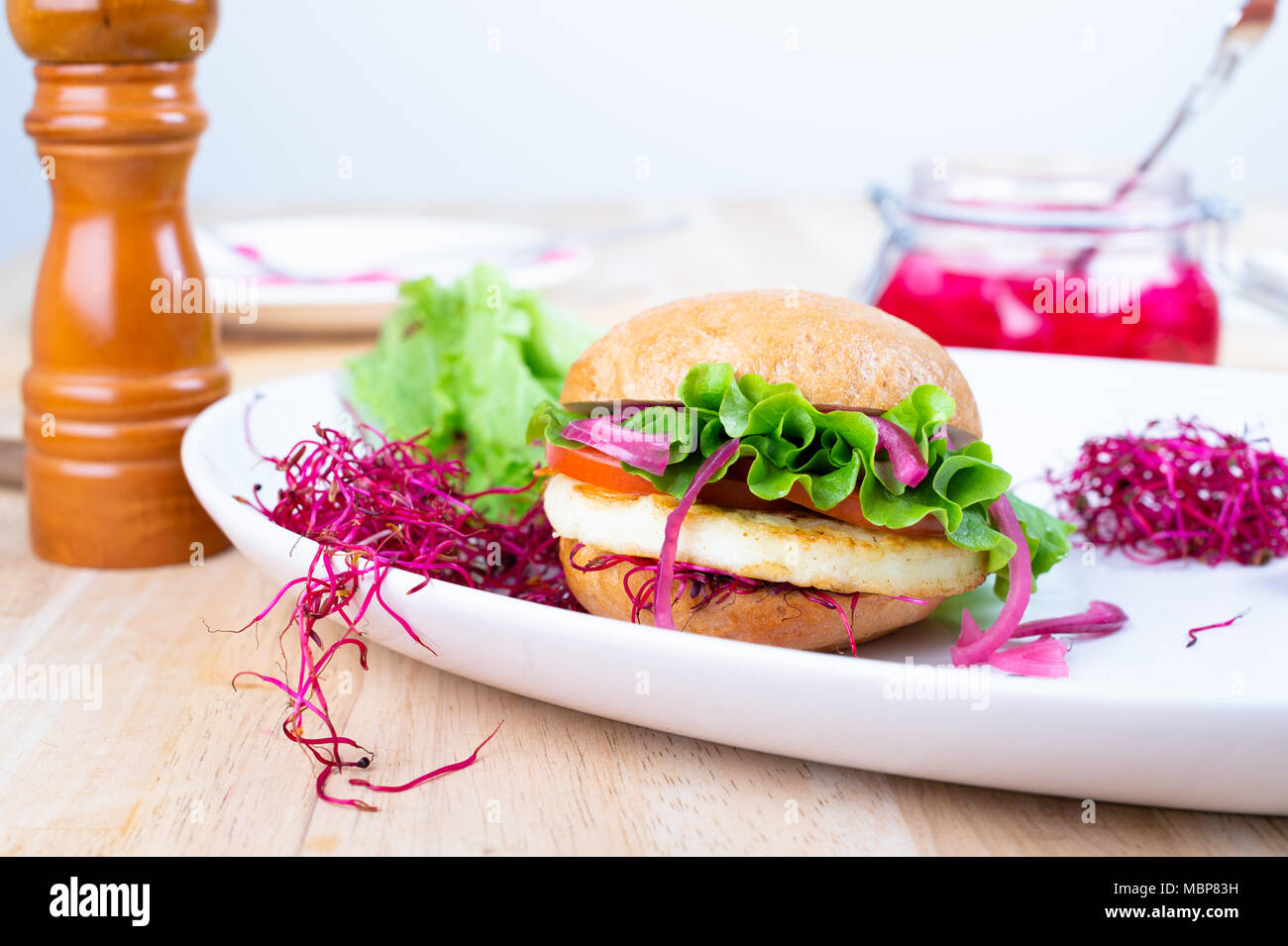 Halloumi burger with lettuce, tomato, pickled red onion and beet sprouts. - Stock Image