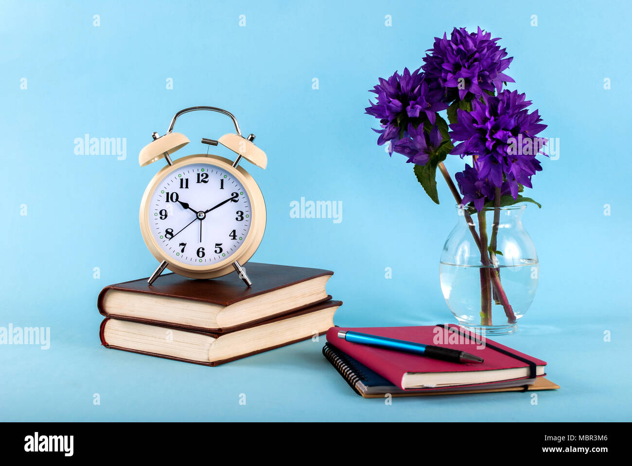 Old clock on books, blue flower color and notebooks isolated on blue ...