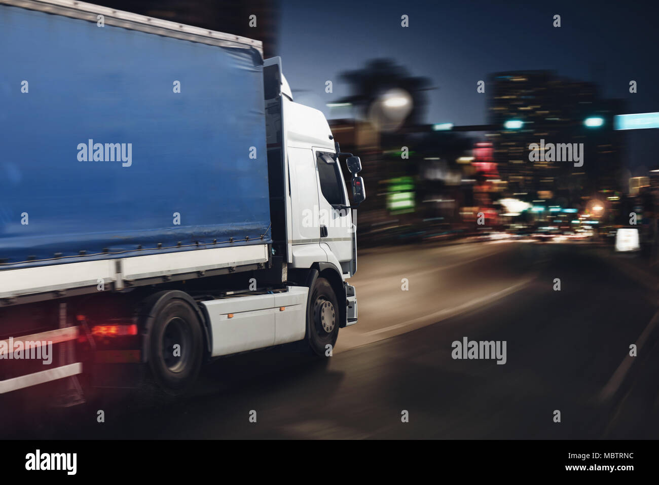 Fast truck on a city road delivering at night - Stock Image
