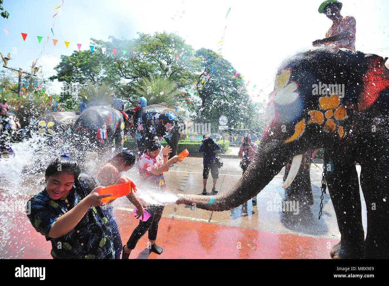 Bangkok, Thailand. 11th Apr, 2018. Elephants spray water on tourists during a celebration for the upcoming Songkran festival in Ayutthaya, Thailand, April 11, 2018. Songkran, also known as the water festival, is celebrated in Thailand as the traditional New Year's day, which will start on April 13. Credit: Rachen Sageamsak/Xinhua/Alamy Live News - Stock Image