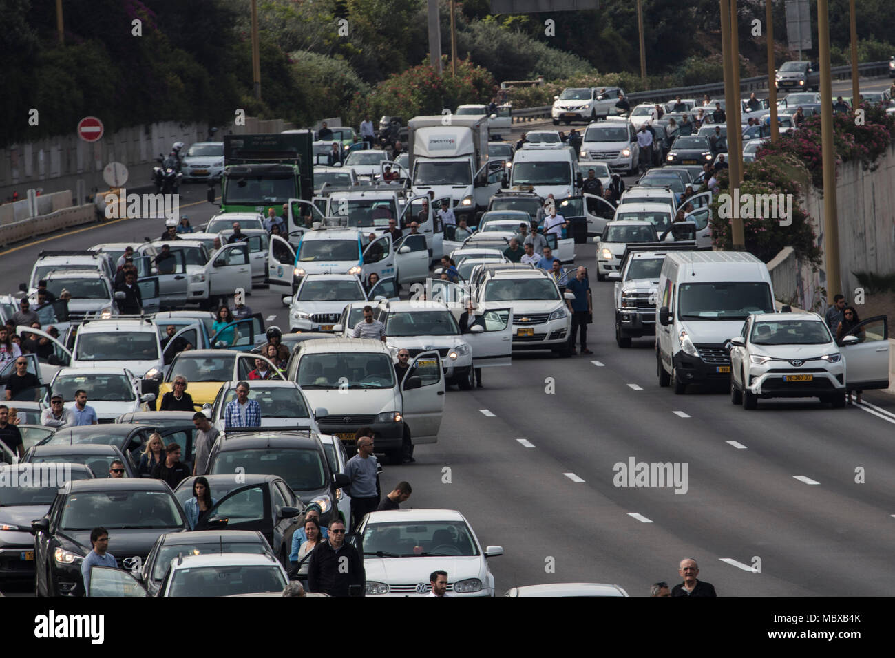 Tel Aviv, Israel. 12th April, 2018. People exit their cars on a highway and observe two minutes of silence to mark the Yom HaShoah (Holocaust and Heroism Remembrance Day), which commemorates approximately six million Jews who perished in the Holocaust that was carried out by Nazis, in Tel Aviv, Israel, 12 April 2018. Yom HaShoah is an annual occasion on which an air raid siren sounds throughout the whole country. While almost everything comes to a complete halt, Israelis are expected to observe two minutes of solemn reflection while the siren is sounded. Credit: dpa picture alliance/Alamy Live - Stock Image