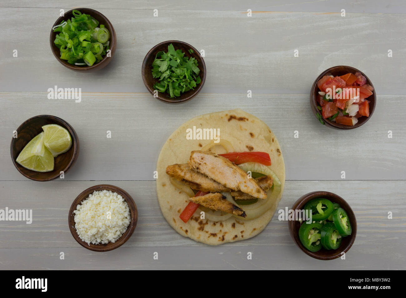 Looking Down on Single Fajita and Toppings on wooden background - Stock Image