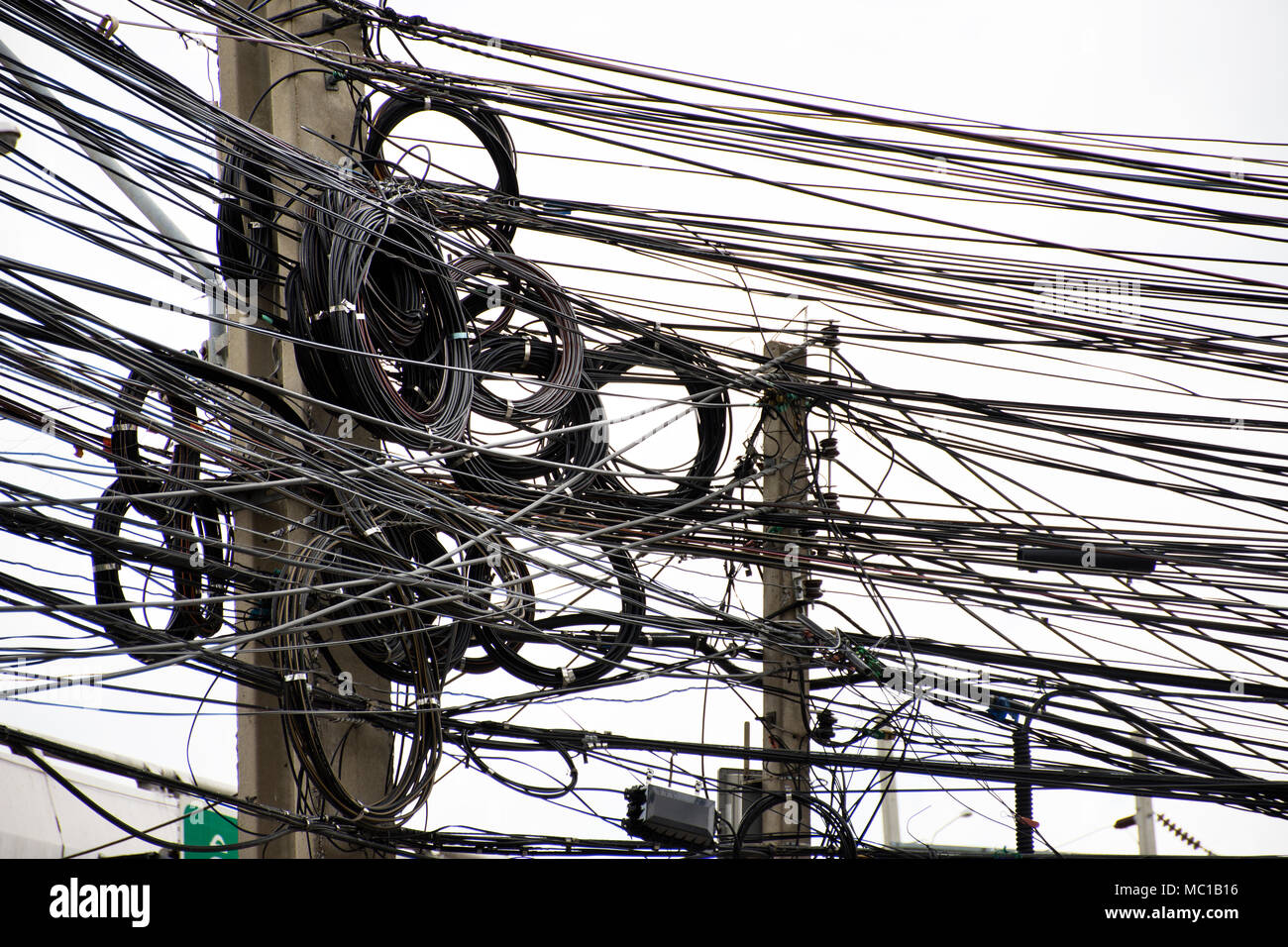 Many Wires Messy With Power Line Cables Transformers And Phone Wiring Lines On Old Electricity Pillar Or Utility Pole At Beside Road In Bangkok Thailand