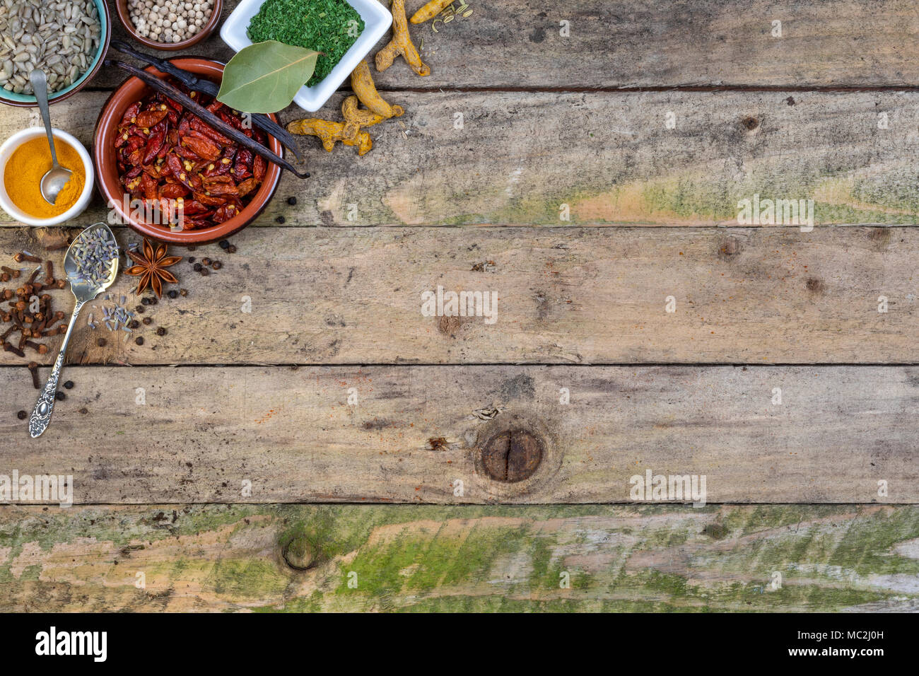 Herbs and Spices with space for text on rustic tabletop. - Stock Image