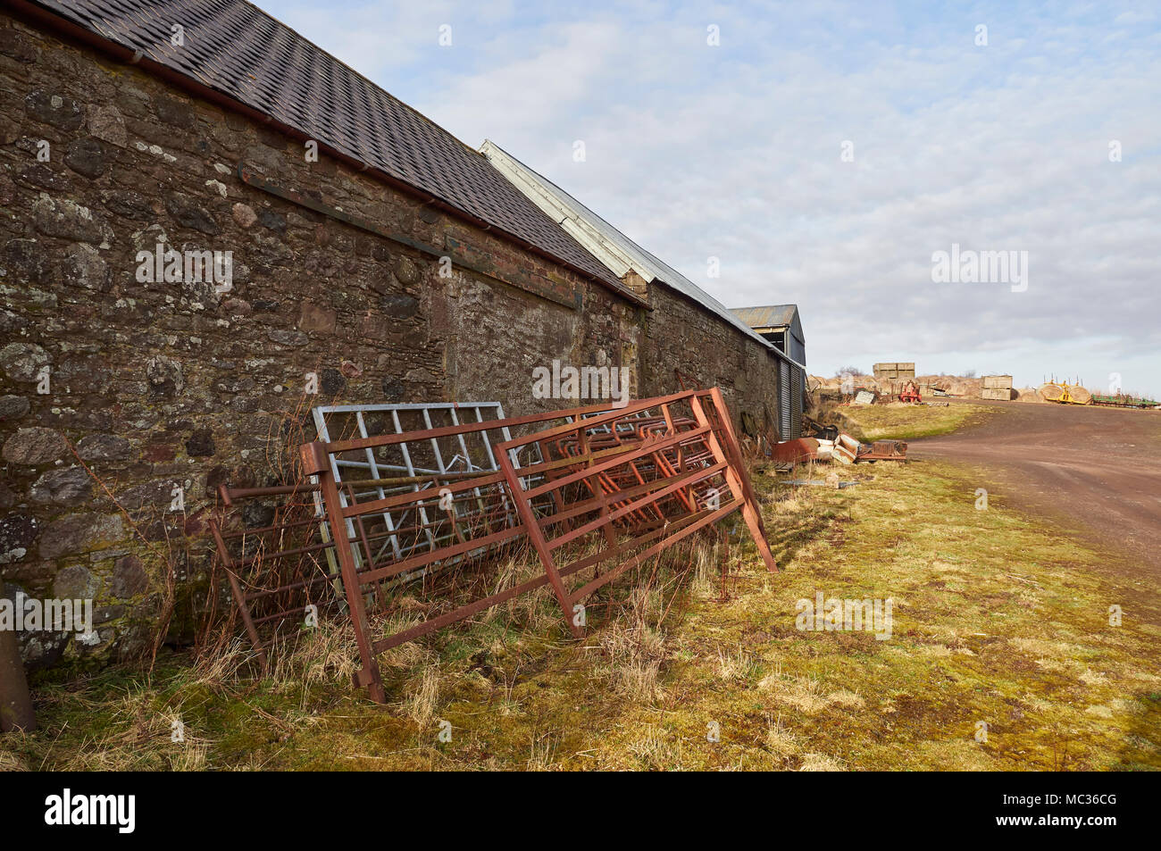 inside barn background. old metal farm gates stacked against a wall of stone built outbuilding with other inside barn background
