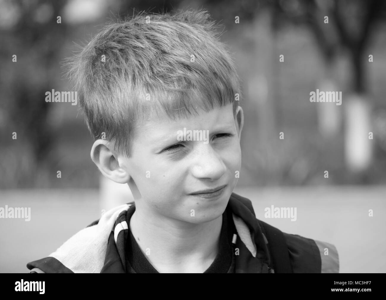 Black and white photo of a serious boy. - Stock Image