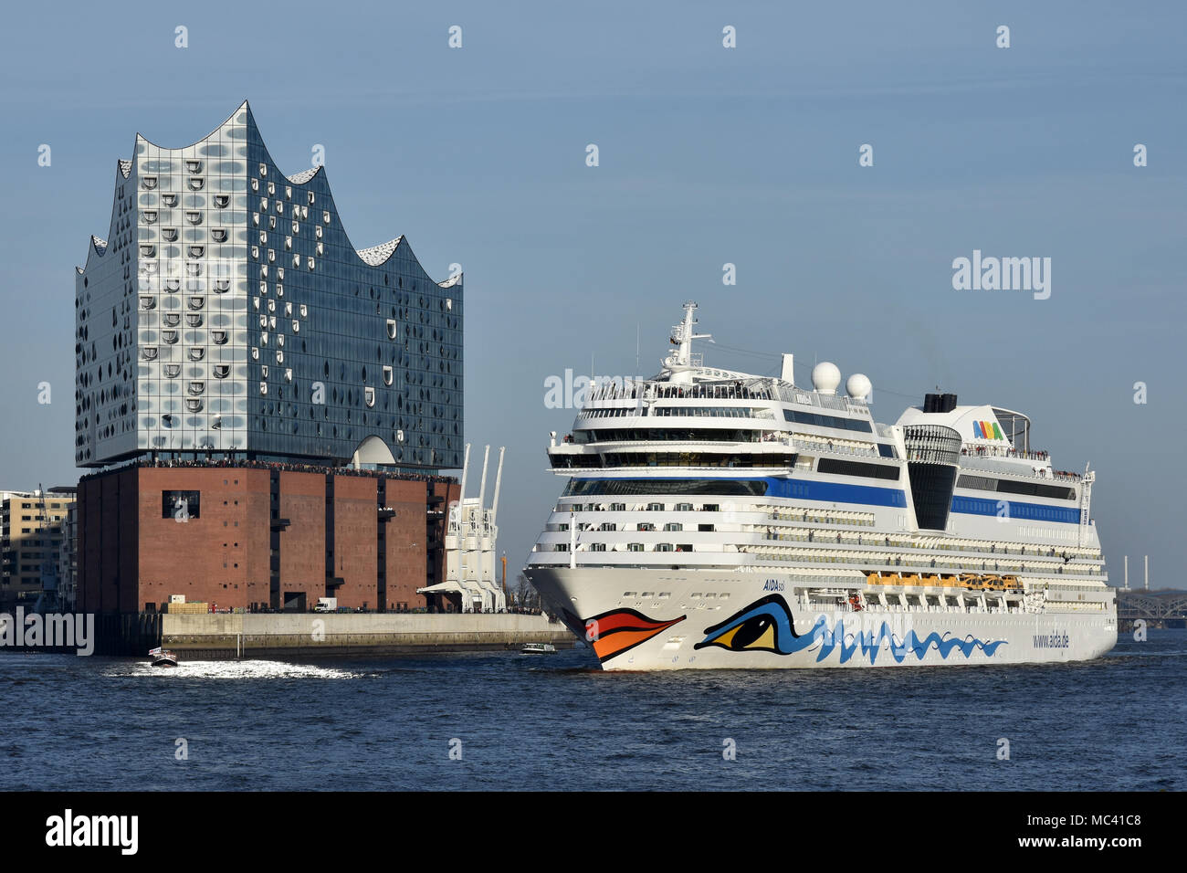 AIDAsol outbound from Hamburg passing the Elbphilharmonie concert hall - Stock Image