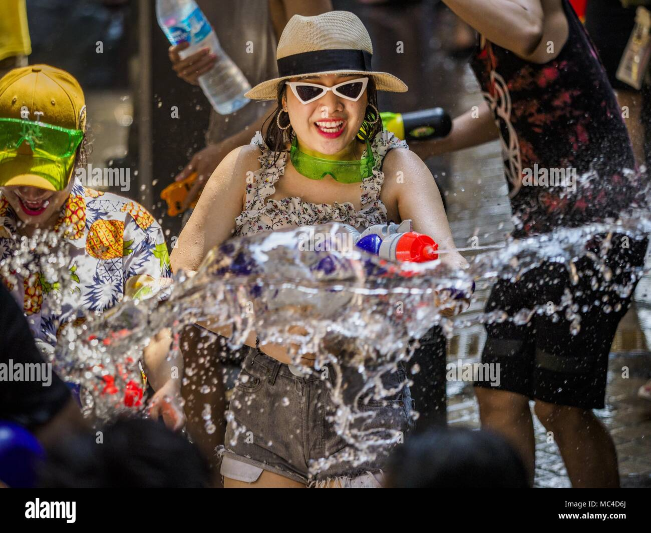 Bangkok, Bangkok, Thailand. 13th Apr, 2018. A woman walks through a water fight on Silom Road during the first day of Songkran in Bangkok. Songkran is the traditional Thai New Year celebration best known for water fights. Credit: Jack Kurtz/ZUMA Wire/Alamy Live News - Stock Image