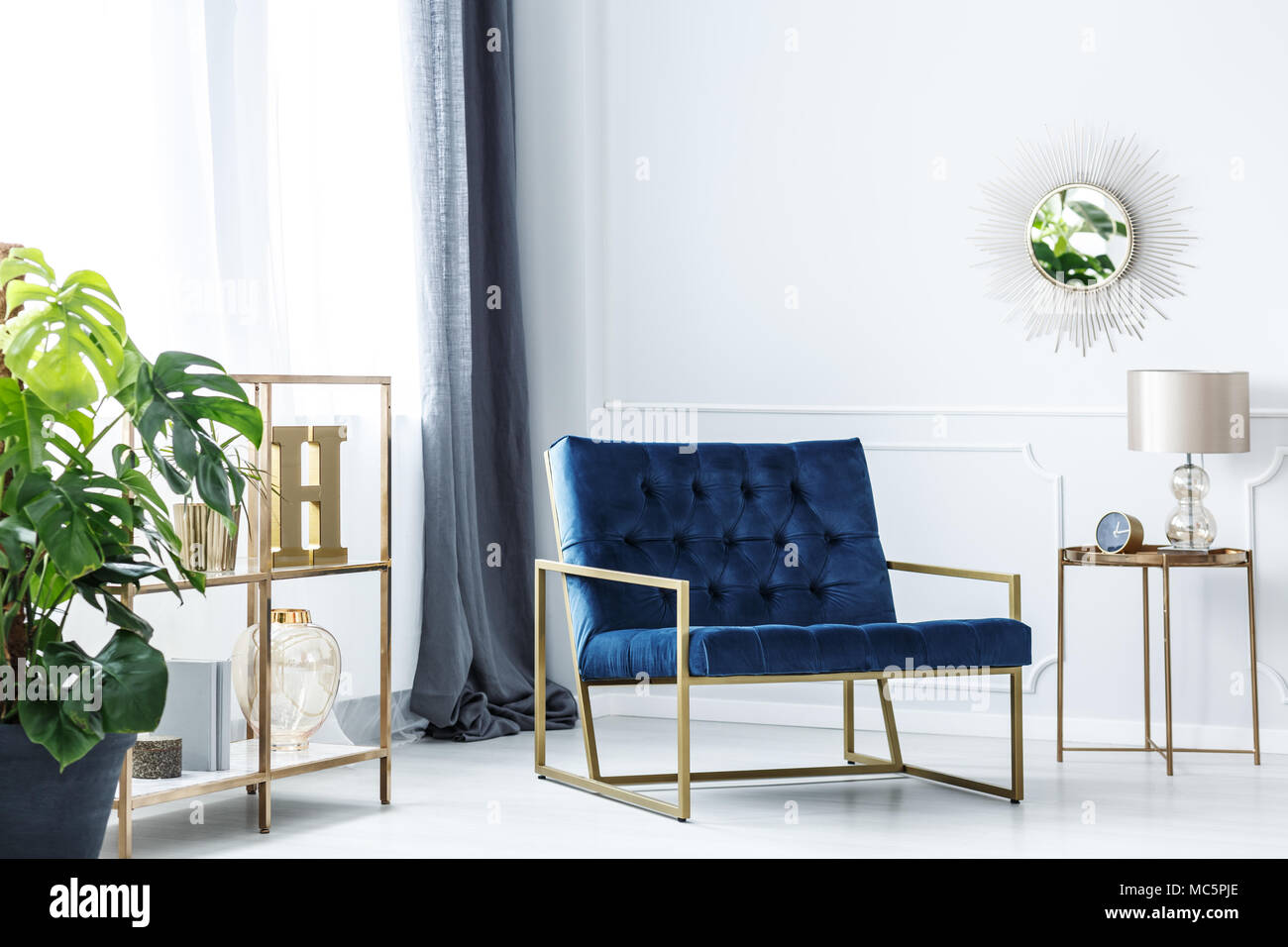 navy blue chair standing in white room interior with golden