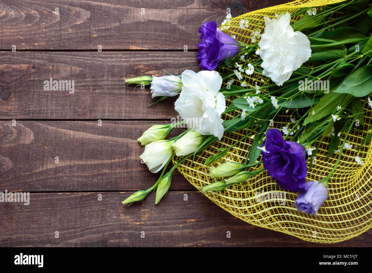 Freshly picked white and purple flowers eustomy lisianthus in the freshly picked white and purple flowers eustomy lisianthus in the form of a bouquet on the wooden background the top view izmirmasajfo