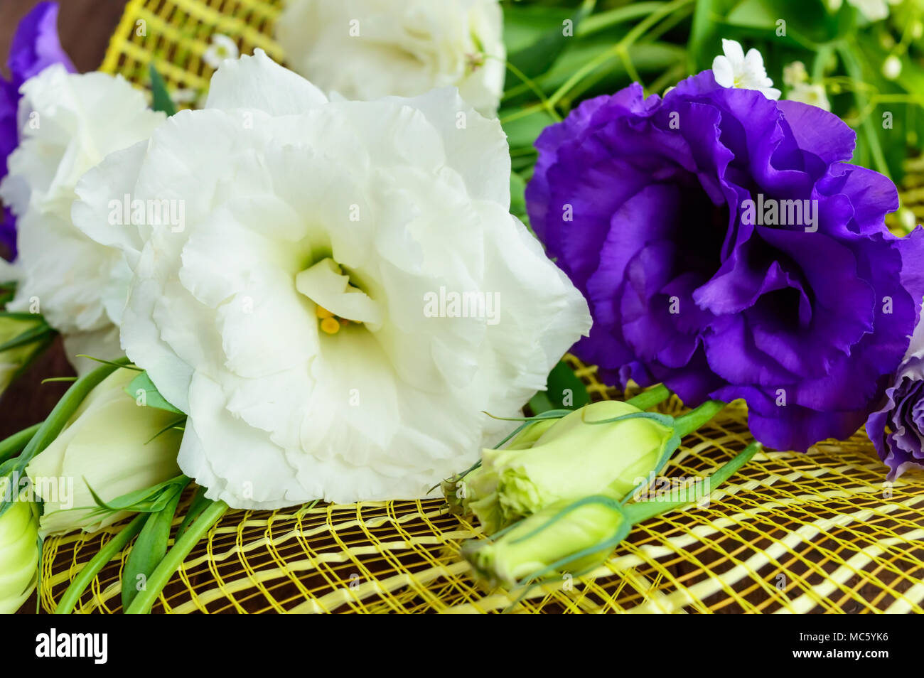 Freshly picked white and purple flowers eustomy lisianthus in the freshly picked white and purple flowers eustomy lisianthus in the form of a bouquet on the wooden background close up izmirmasajfo