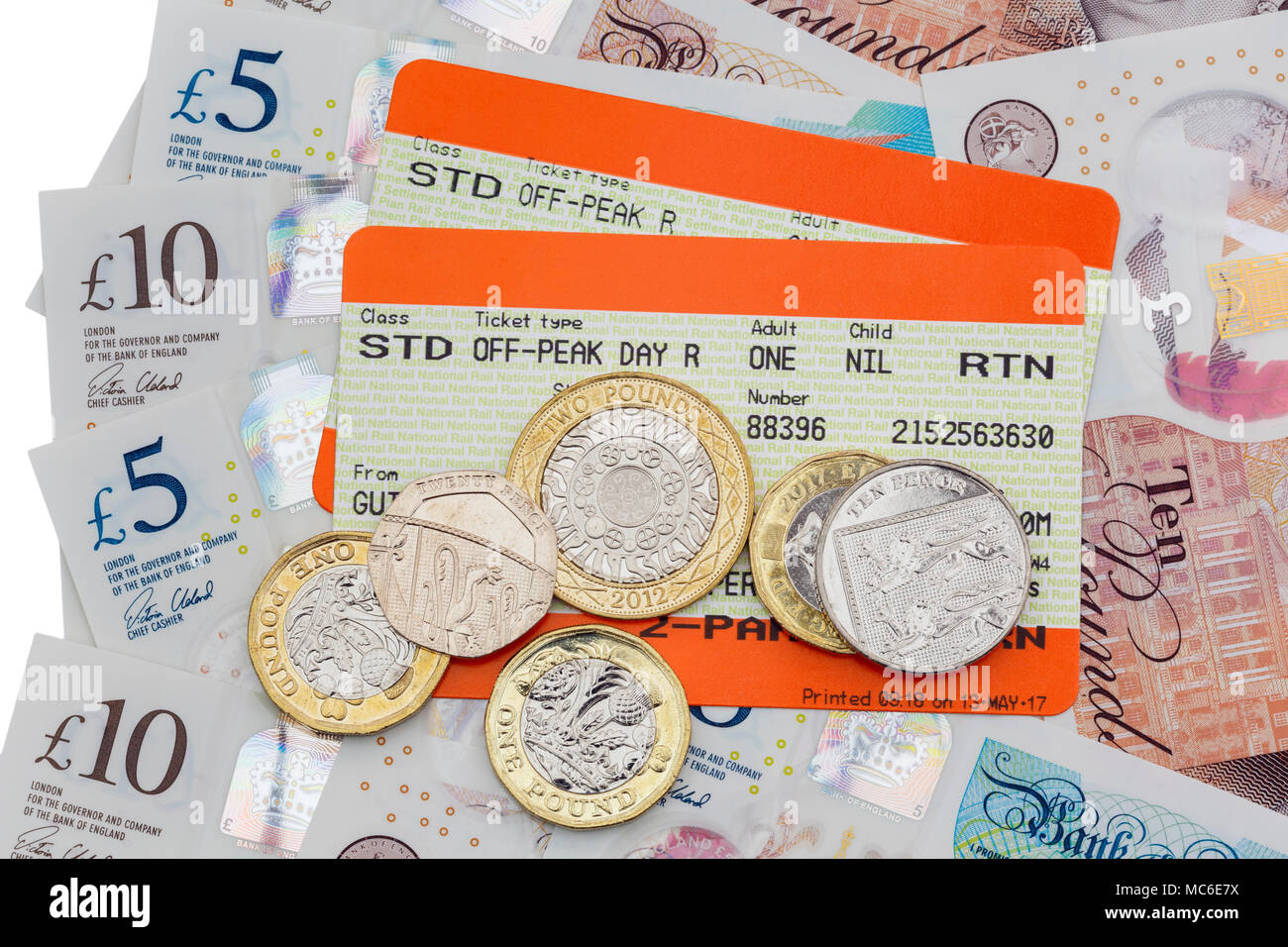 Two British train tickets for Standard off-peak travel out and return rail fares with five and ten pound notes and new pound coins. England UK Britain Stock Photo
