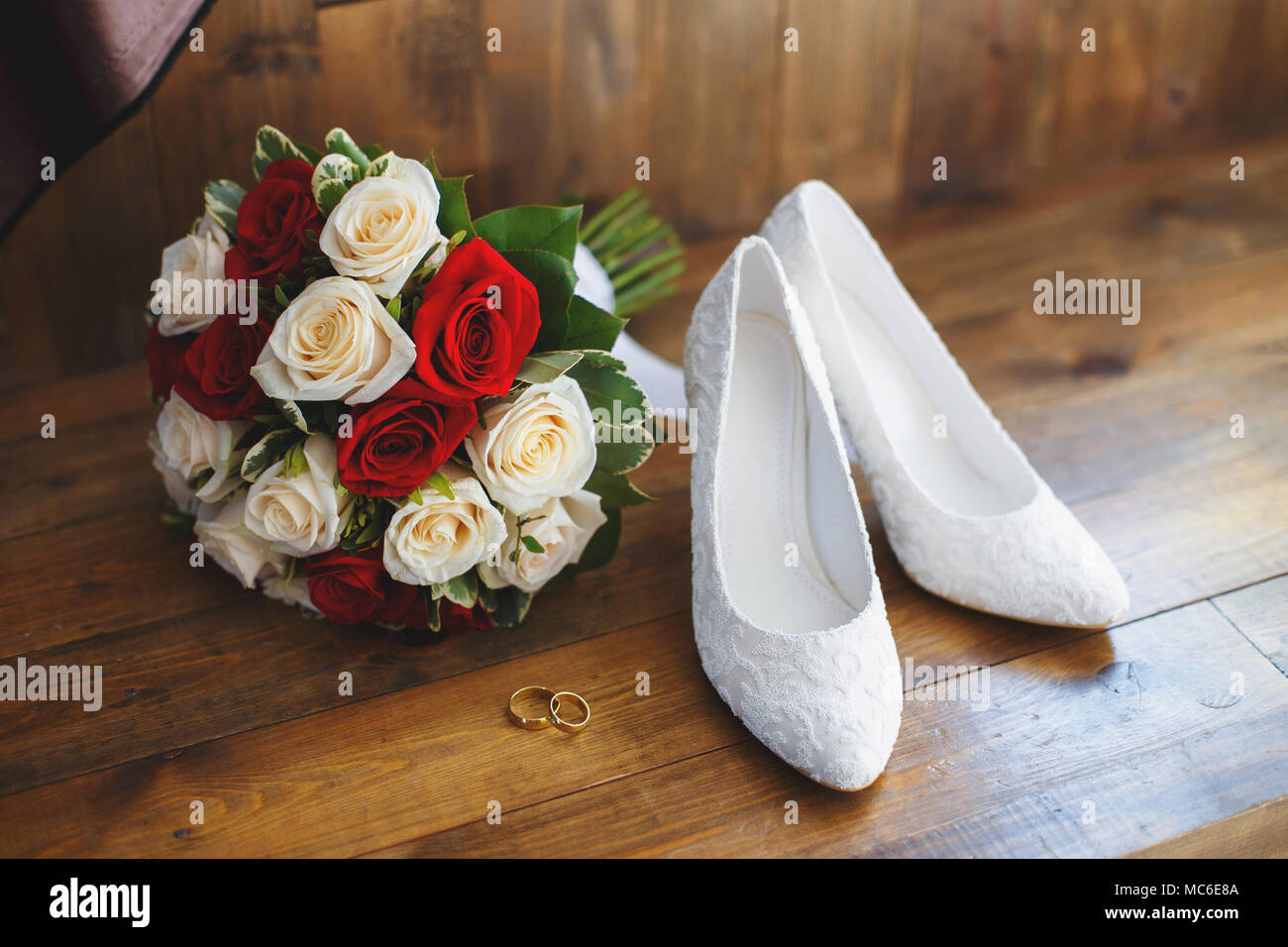 Wedding Shoes And Bouquet Of Red And White Roses On Wooden