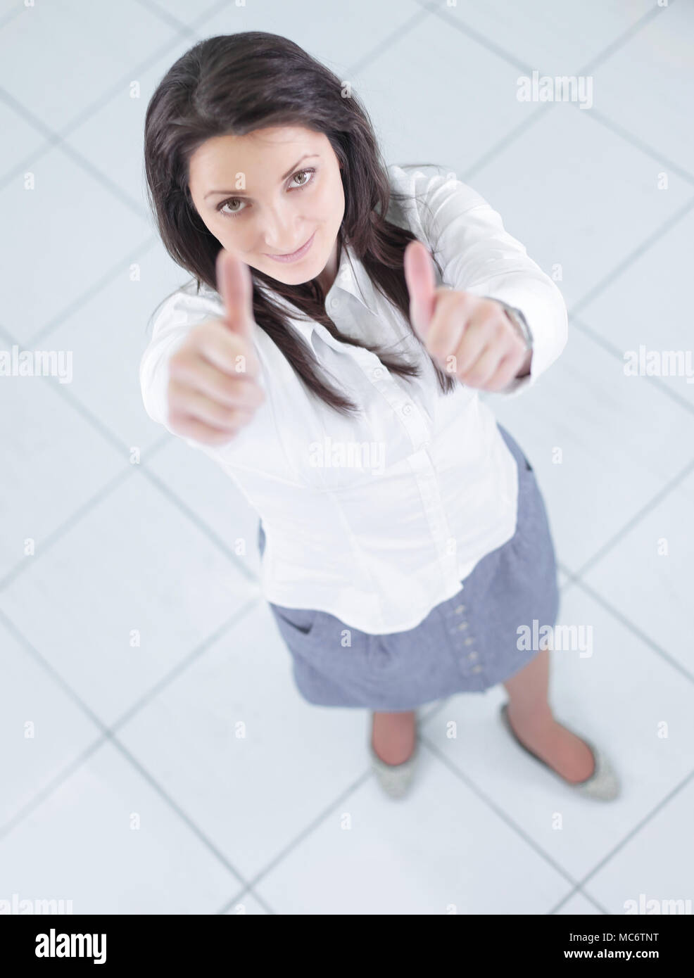 view from the top.in full growth.successful business woman showing thumb up - Stock Image