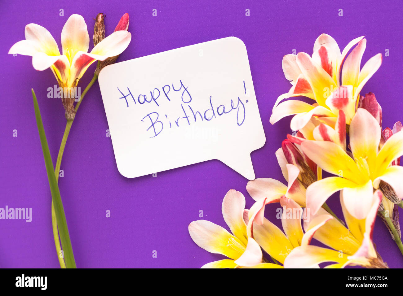 Note in shape of heart with words happy birthday with flowers on note in shape of heart with words happy birthday with flowers on purple surface izmirmasajfo