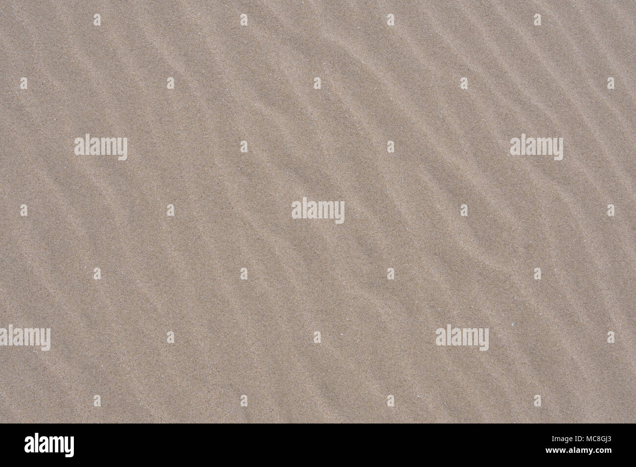 Soft Ripples in Sand Along Pacific Coast Beach Background Image - Stock Image