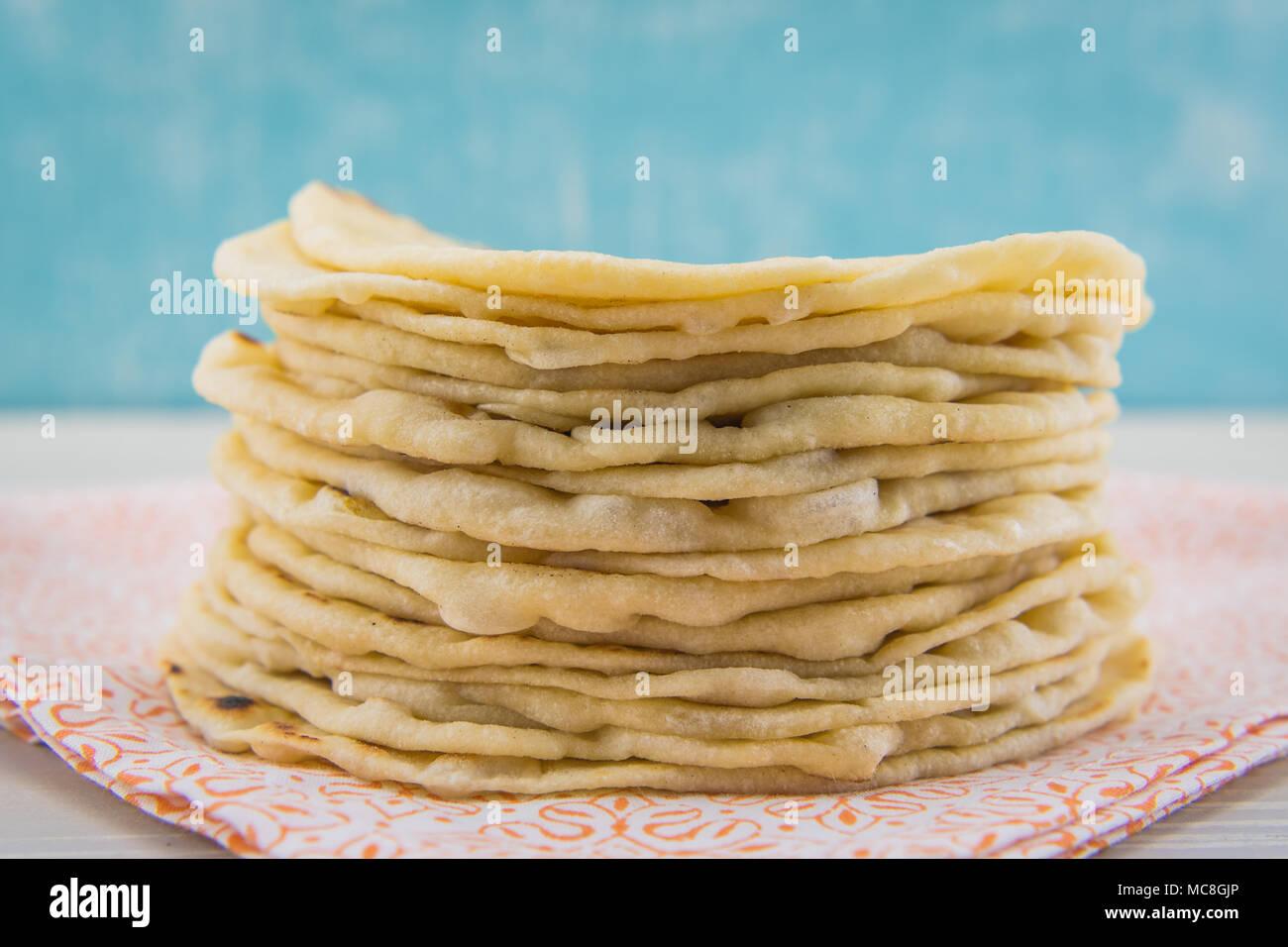 Stack of Fresh Floud Tortillas on Orange Cloth - Stock Image