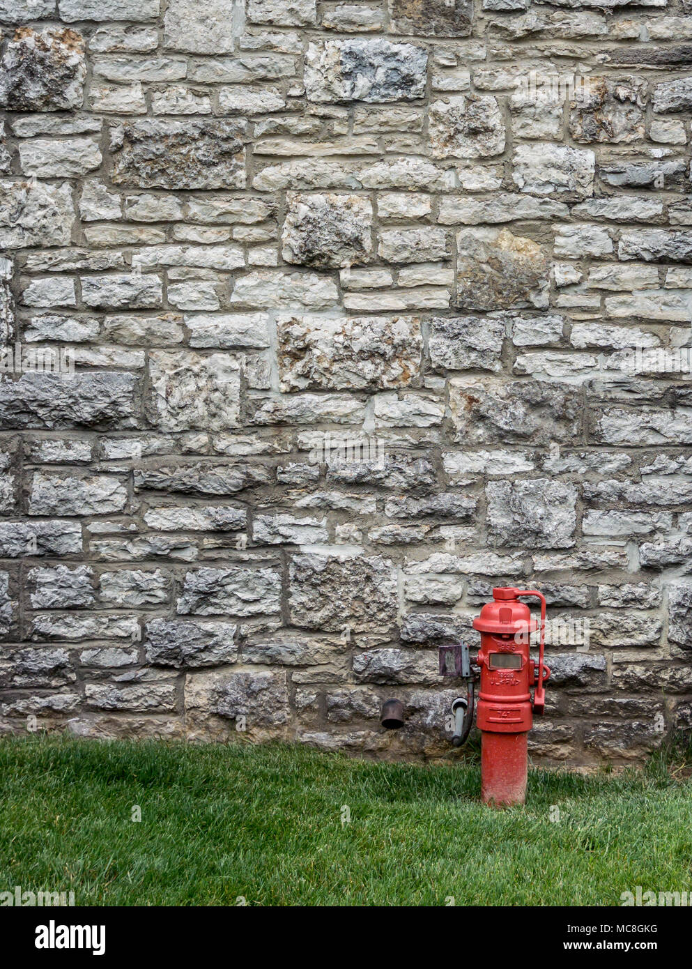 A red fire hydrant contrasts against an aged stone wall at a distillery along the bourbon trail - Stock Image