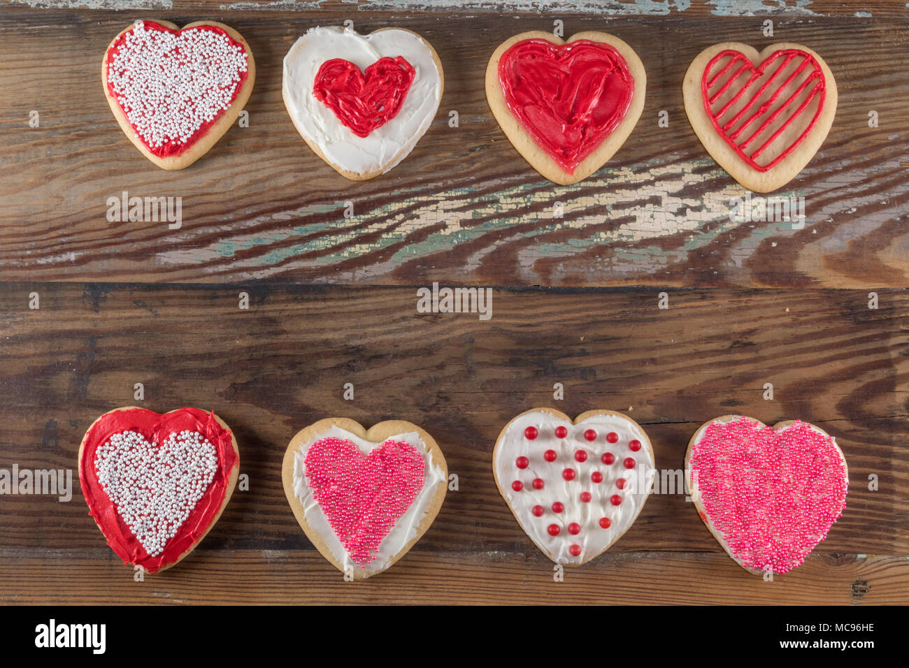 Two Lines of Decorated Heart Shaped Cookies on wooden background - Stock Image