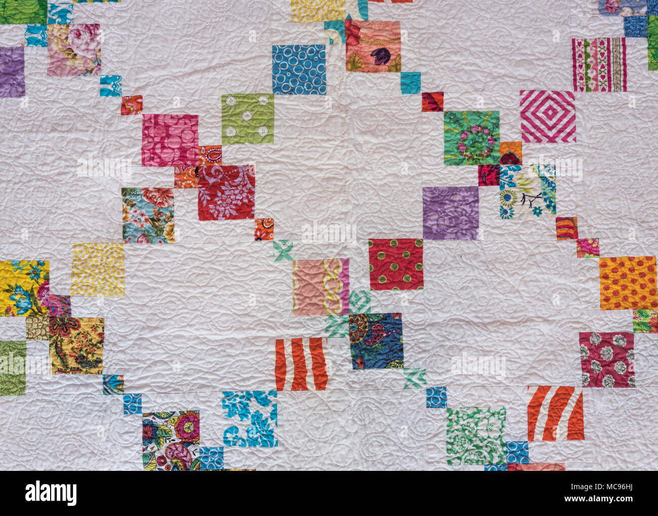 White Quilt with Diagonal Colorful Accents and decorative stitching - Stock Image
